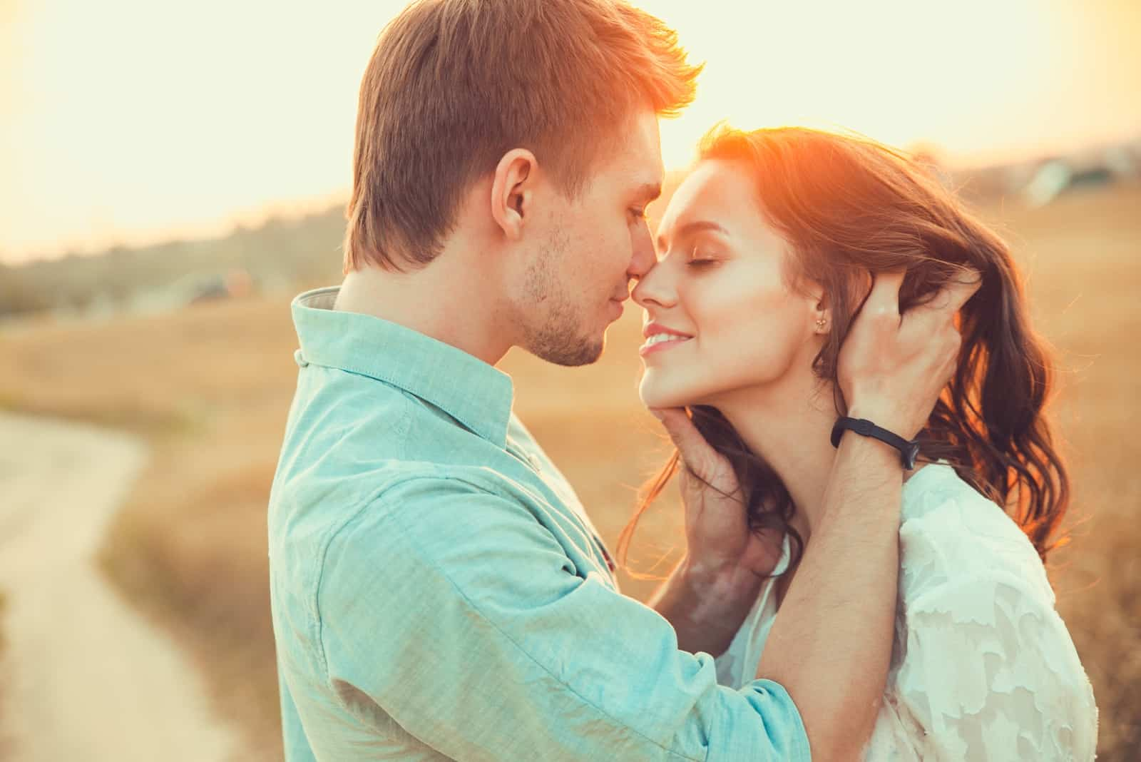 man touching woman's hair while standing near grass field
