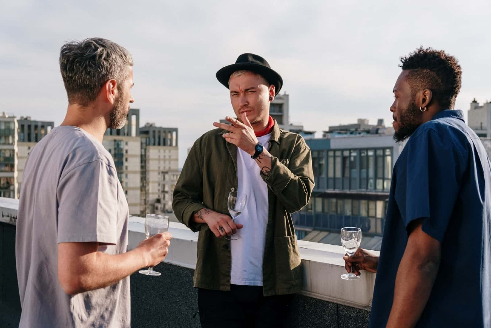 three men talking while standing on rooftop