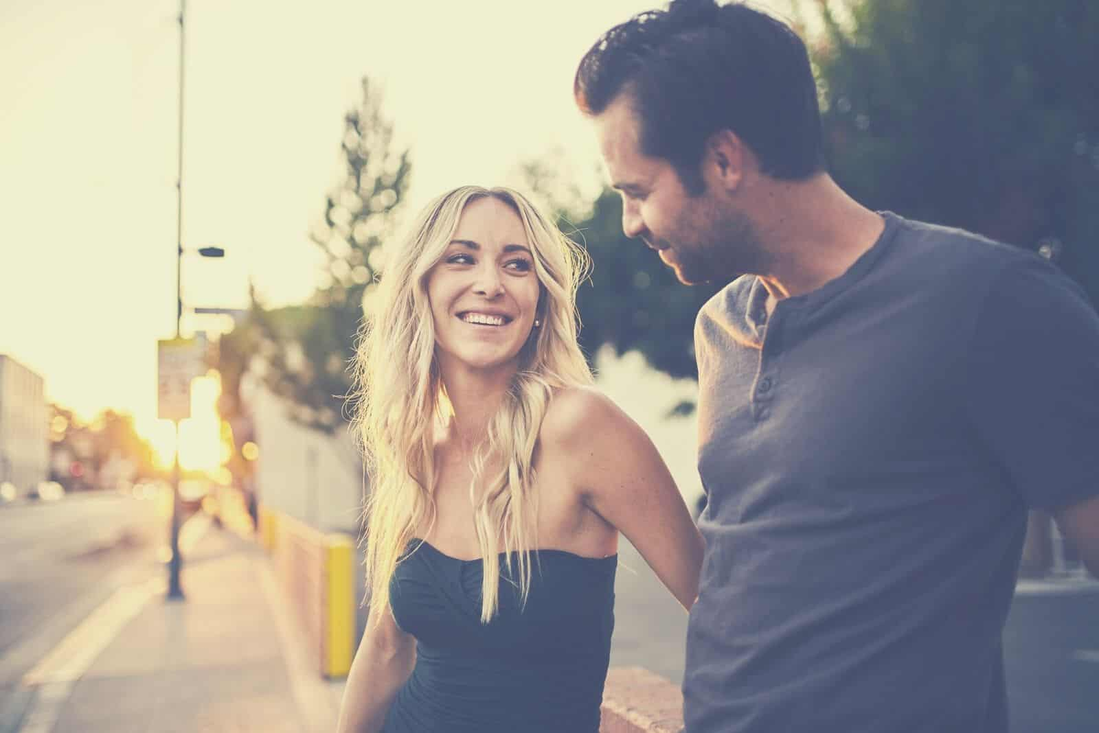 romantic attractive couple looking at each other while standing along the streets