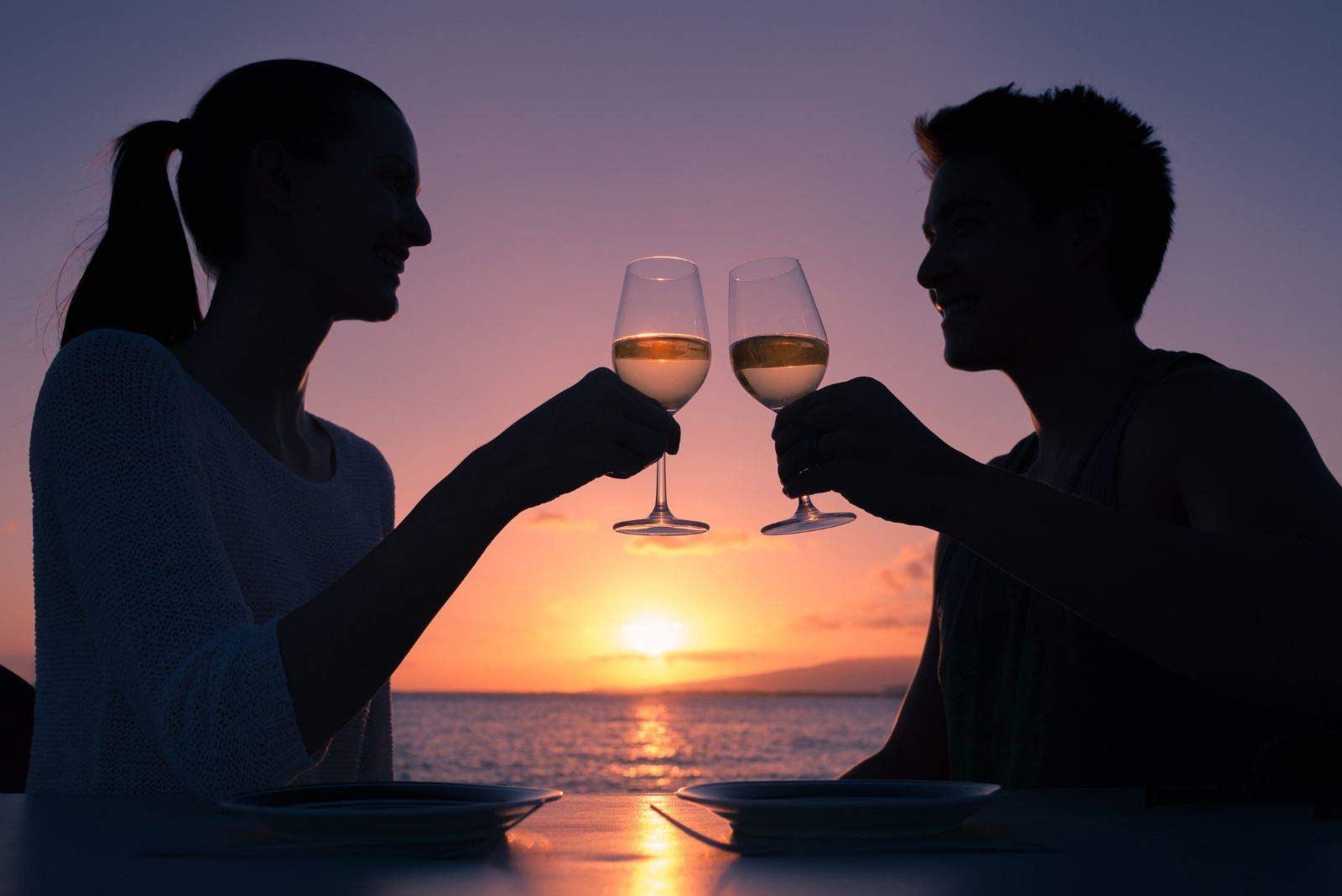 romantic couple having a glass of wine during date by the bay during sunset