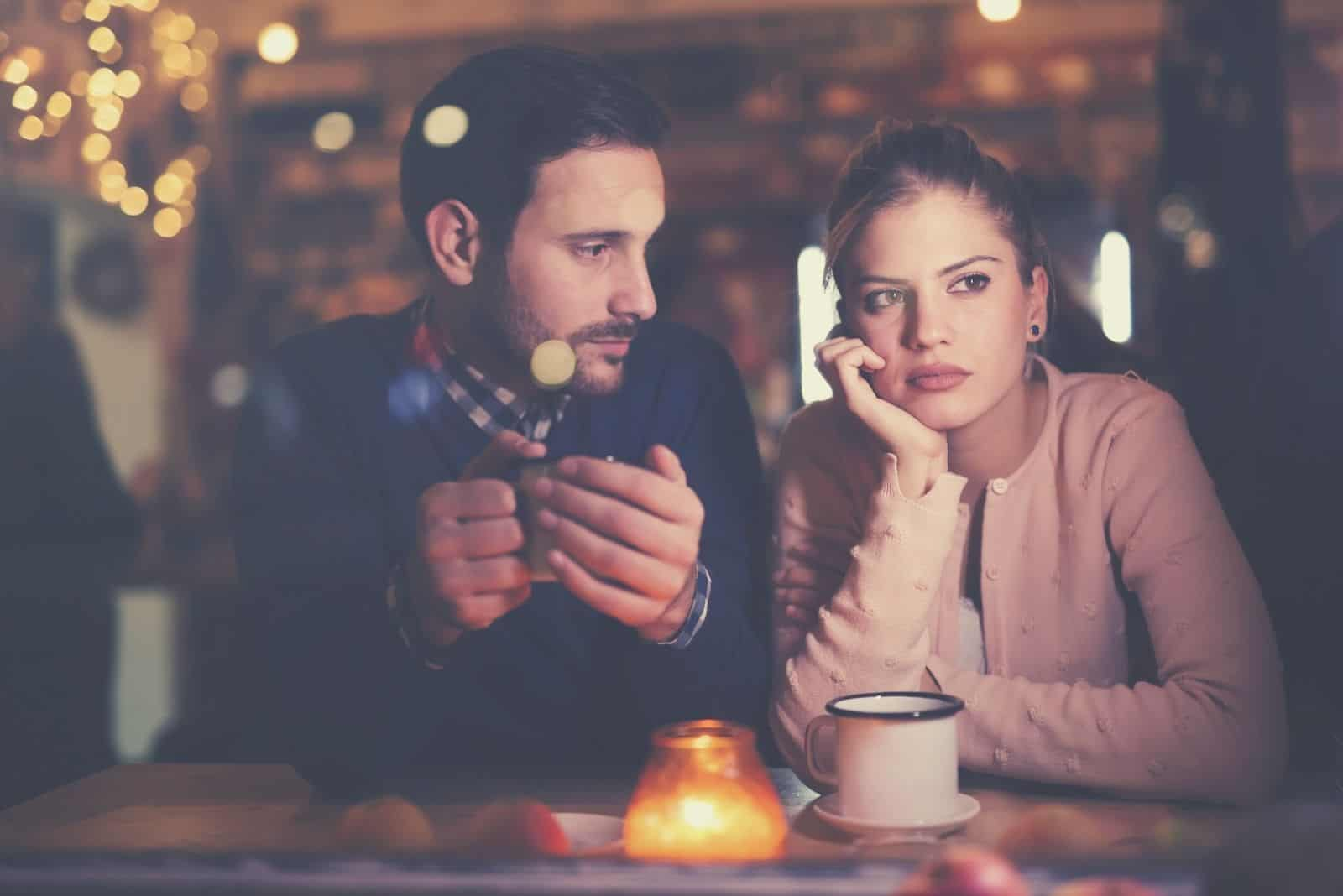 sad couple having conflict inside a restaurant while having a dinner date