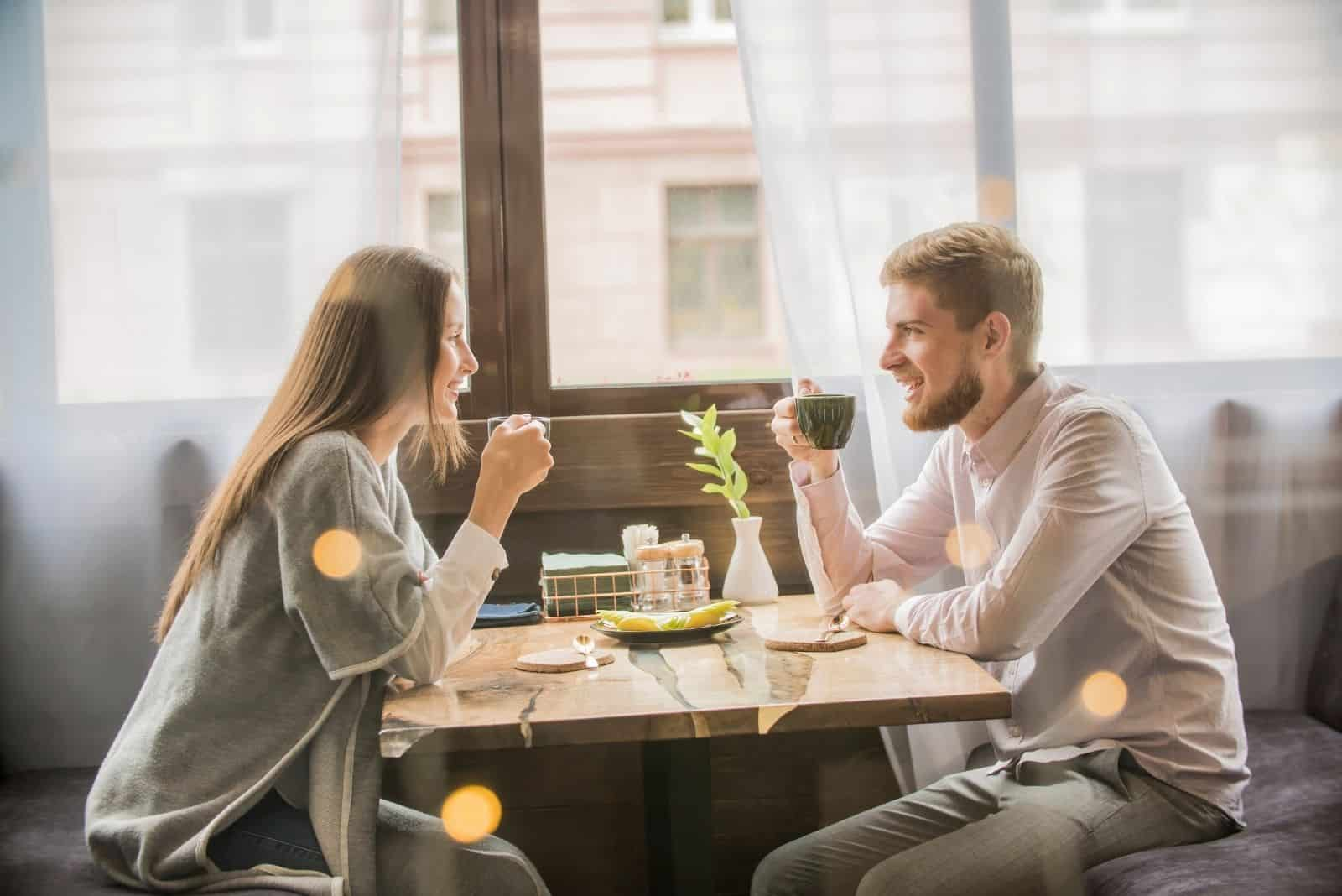 sweet couple drinking coffee in a cafe facing each other