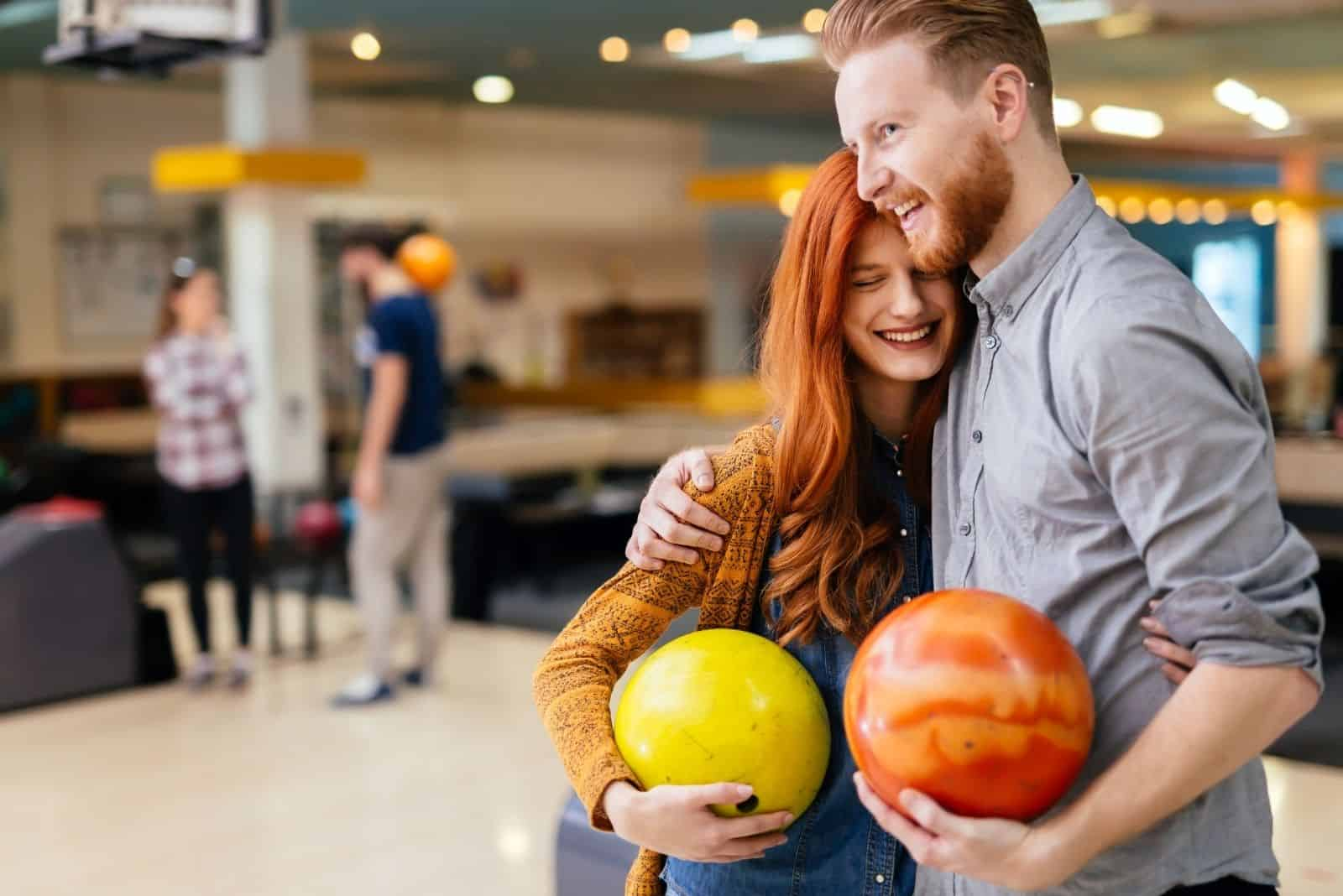 sweet couple hugging inside a bowling alley holding a bowling ball