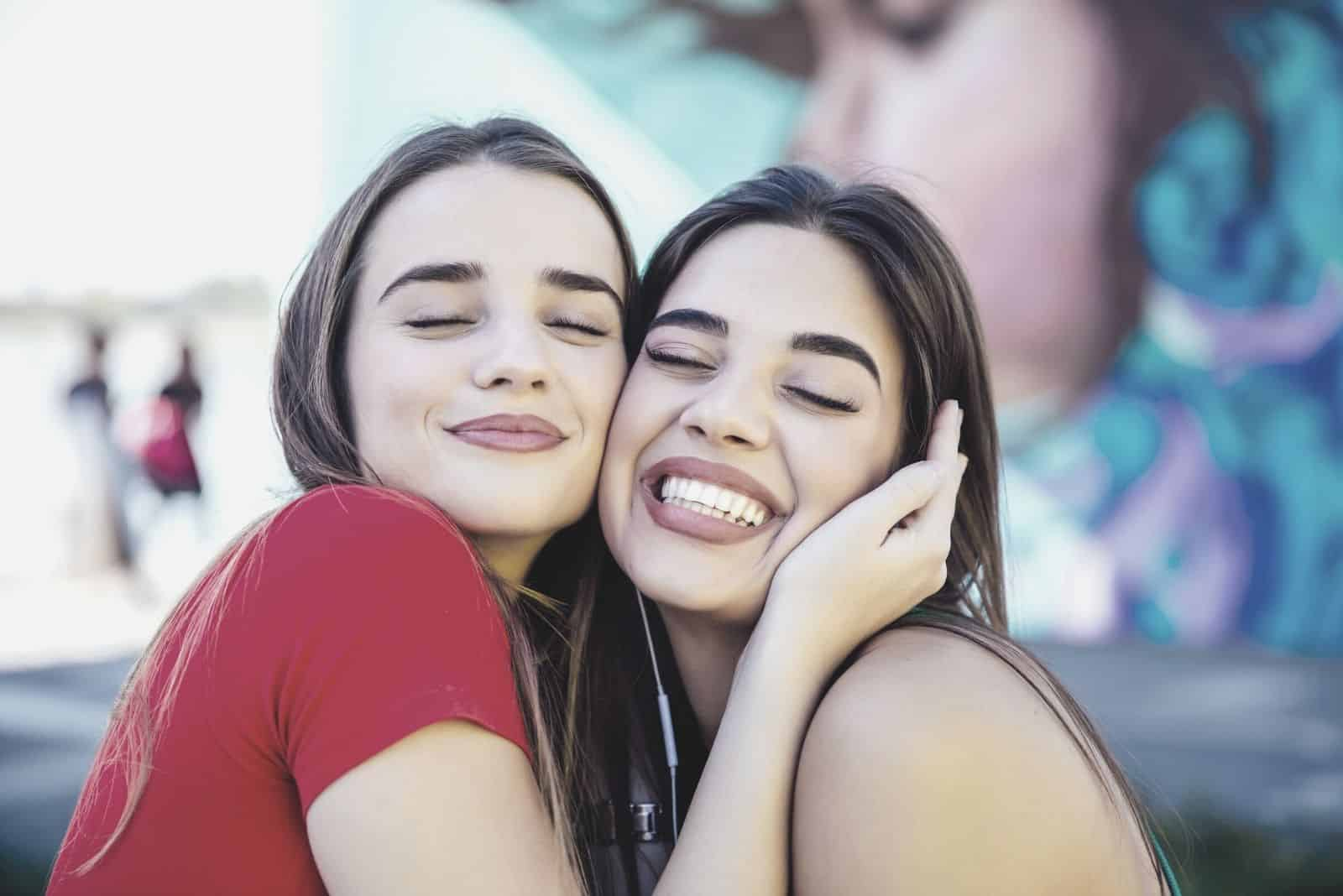 two best female friends hugging each other and closing their eyes in close up photography