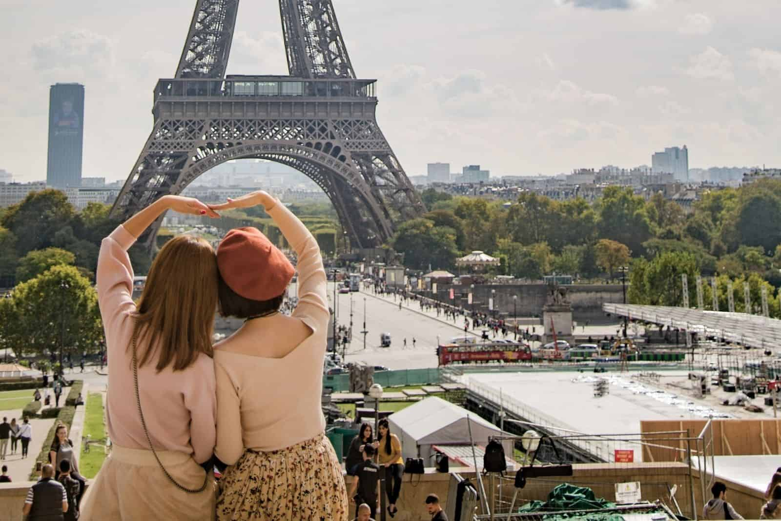 two french women making a heart shaped with their hands facing the Eiffel tower in France