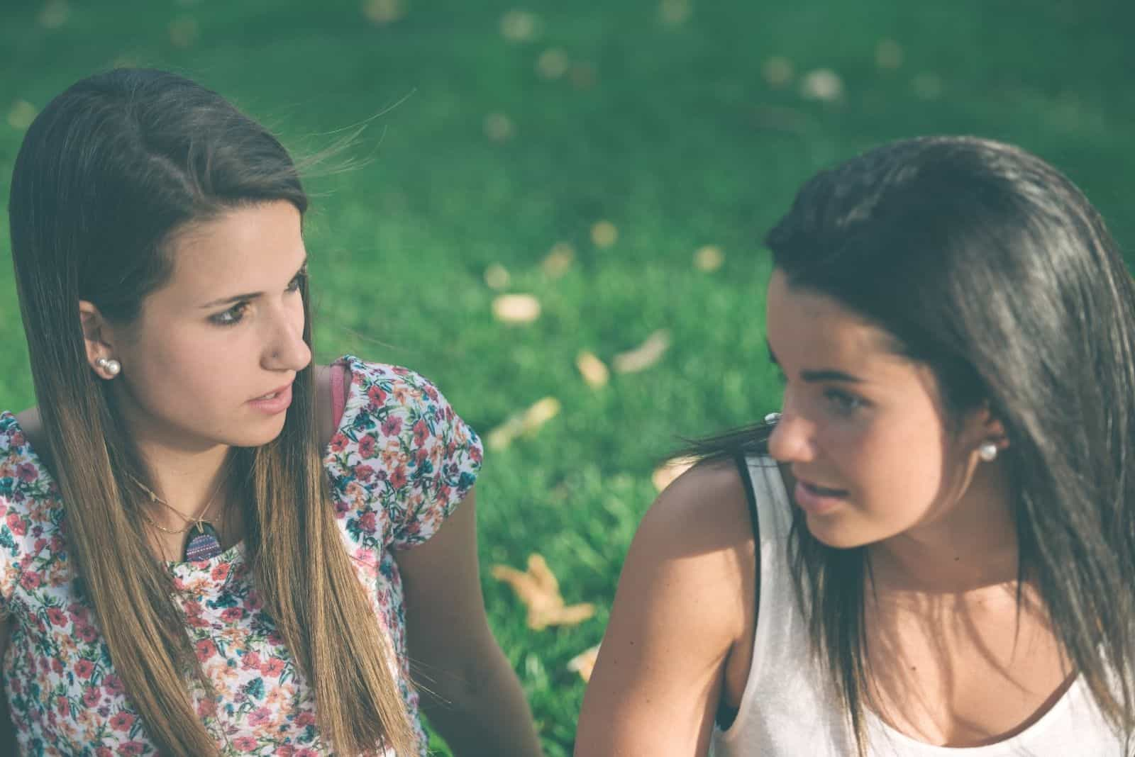 two young friends talking seriously outdoors sitting on the ground