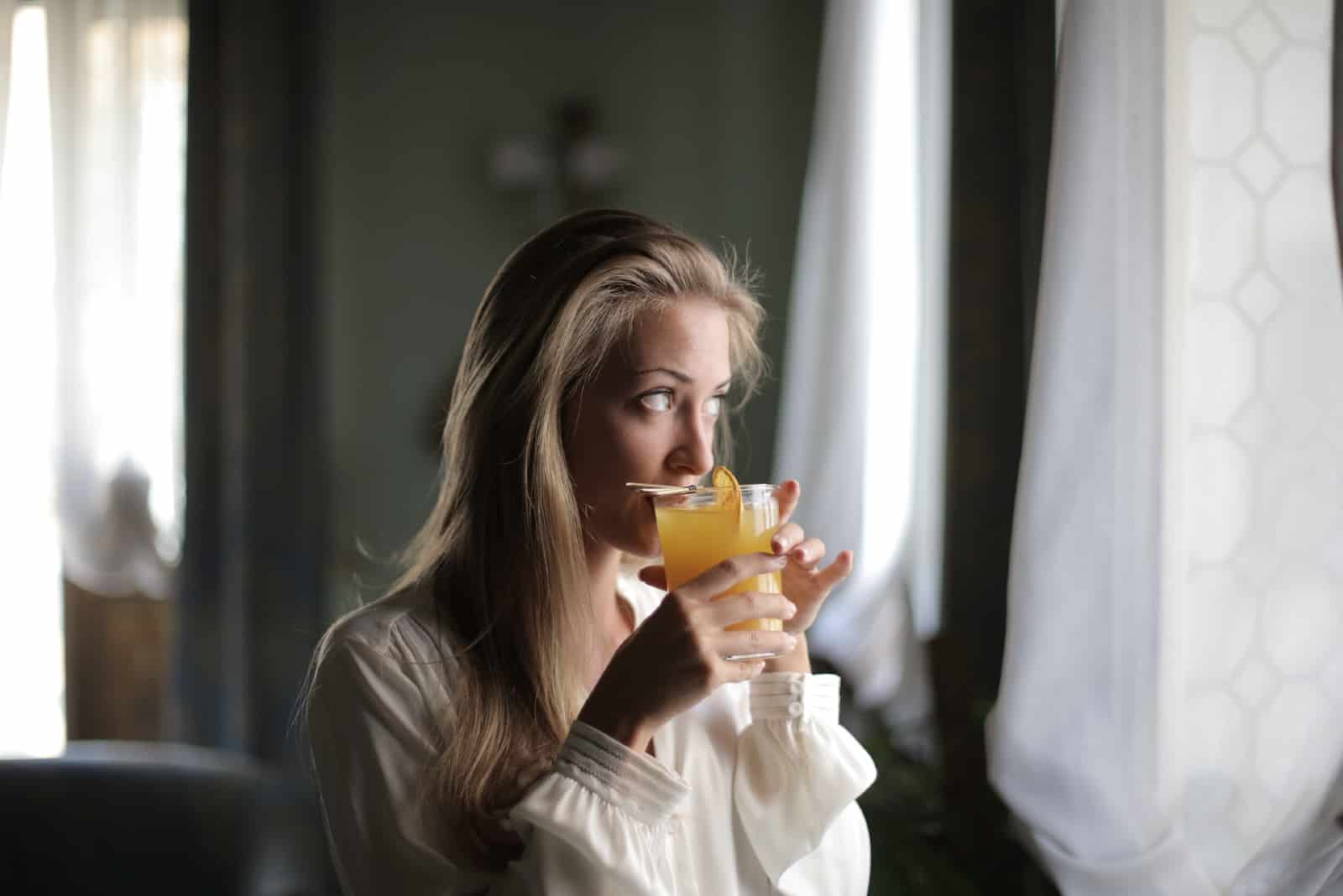 woman drinking orange juice while looking through window