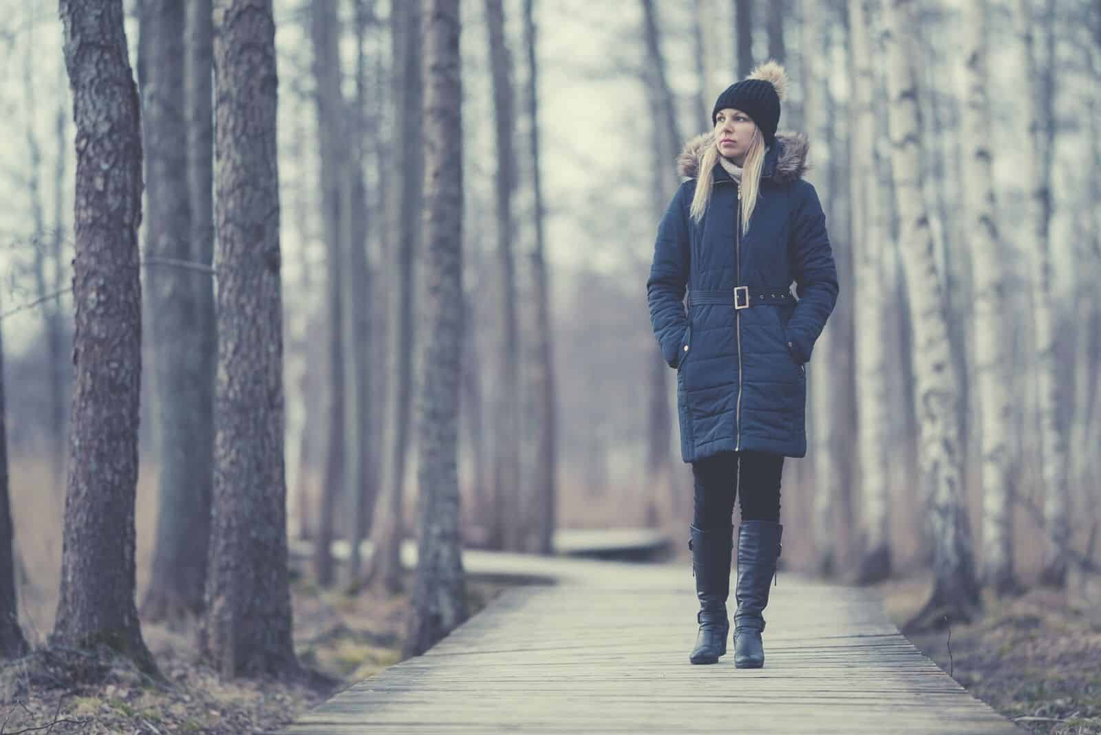 woman in winter clothes walking thru the pathway in the park with tall trees