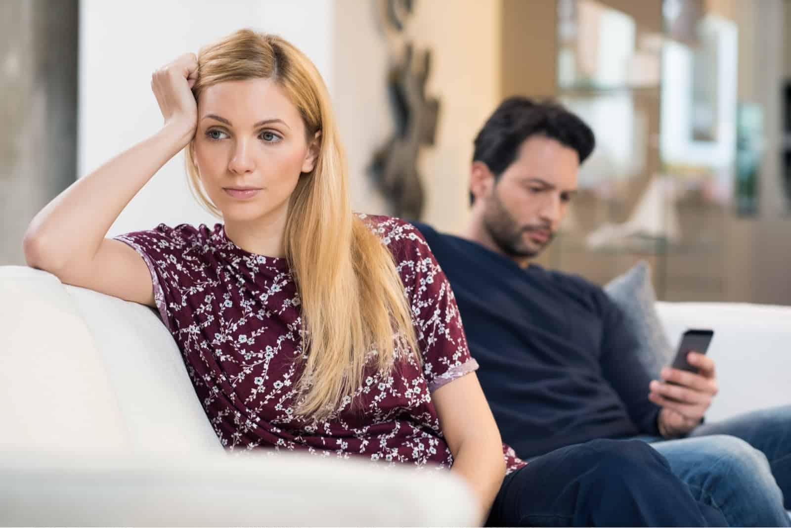 sad woman leaning on sofa while sitting near man