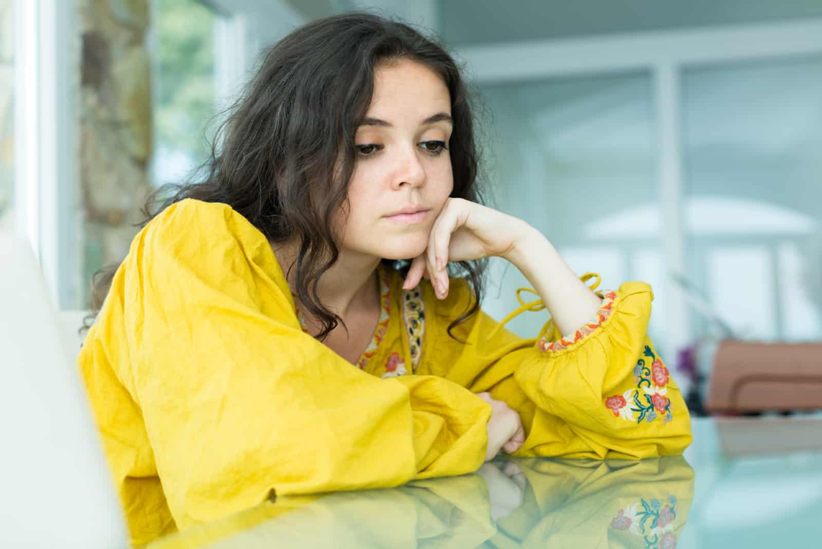 sad woman in yellow blouse leaning on table