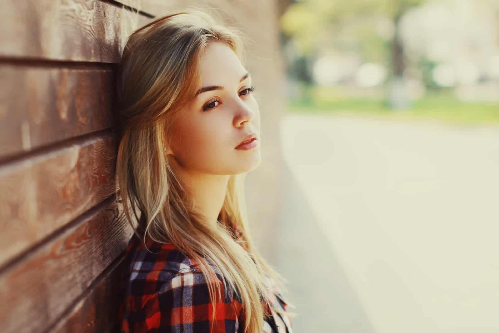 blonde woman in red checked shirt leaning wall