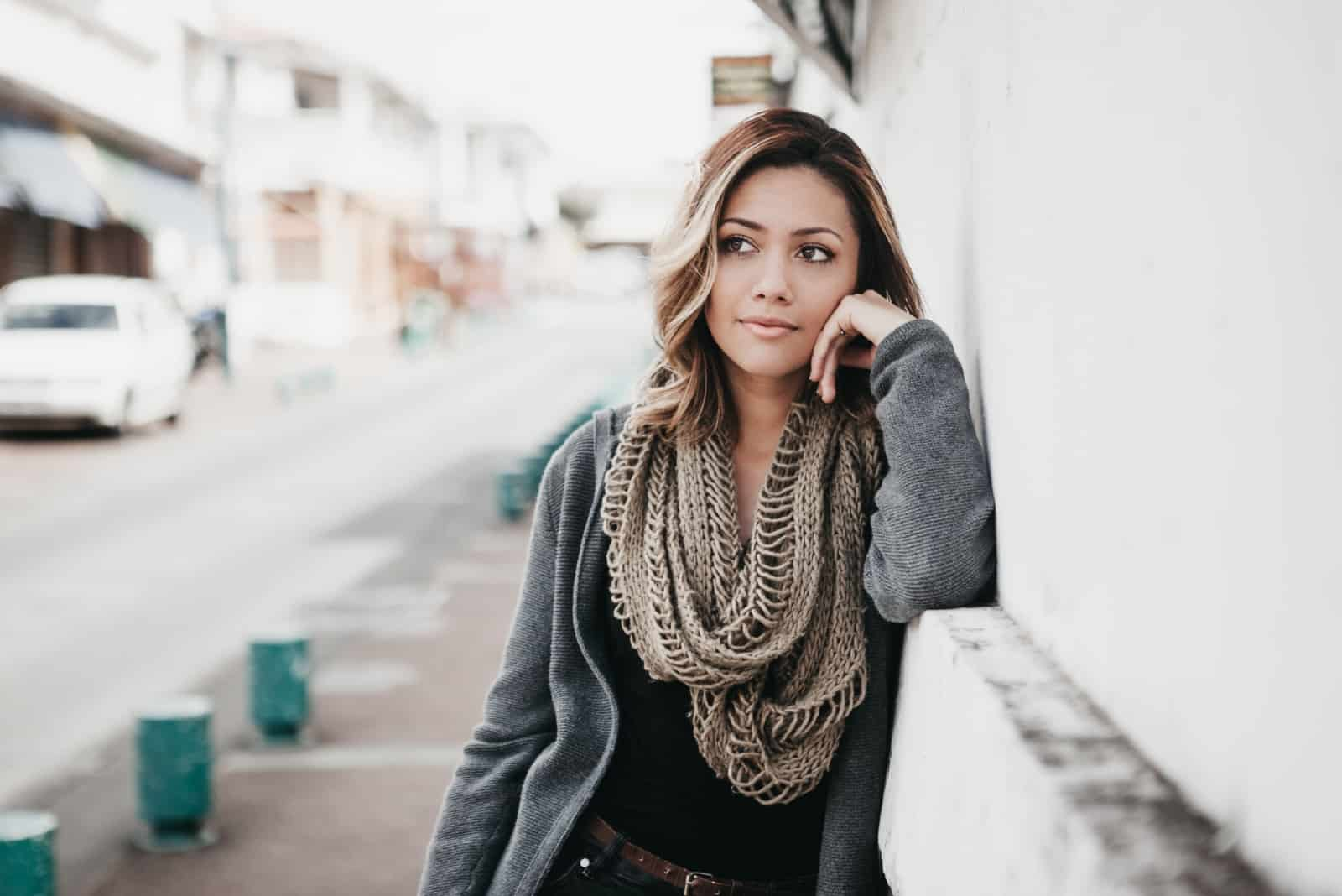 pensive woman with gray scarf leaning on wall