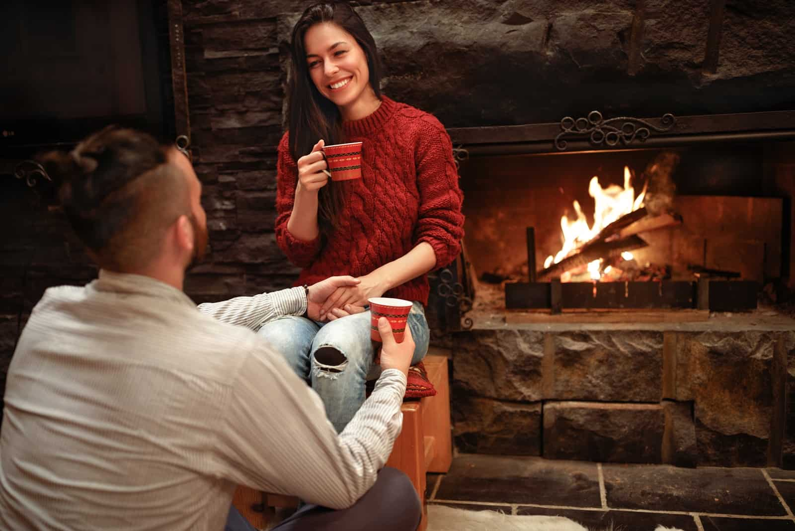 happy woman looking at man while sitting near fireplace