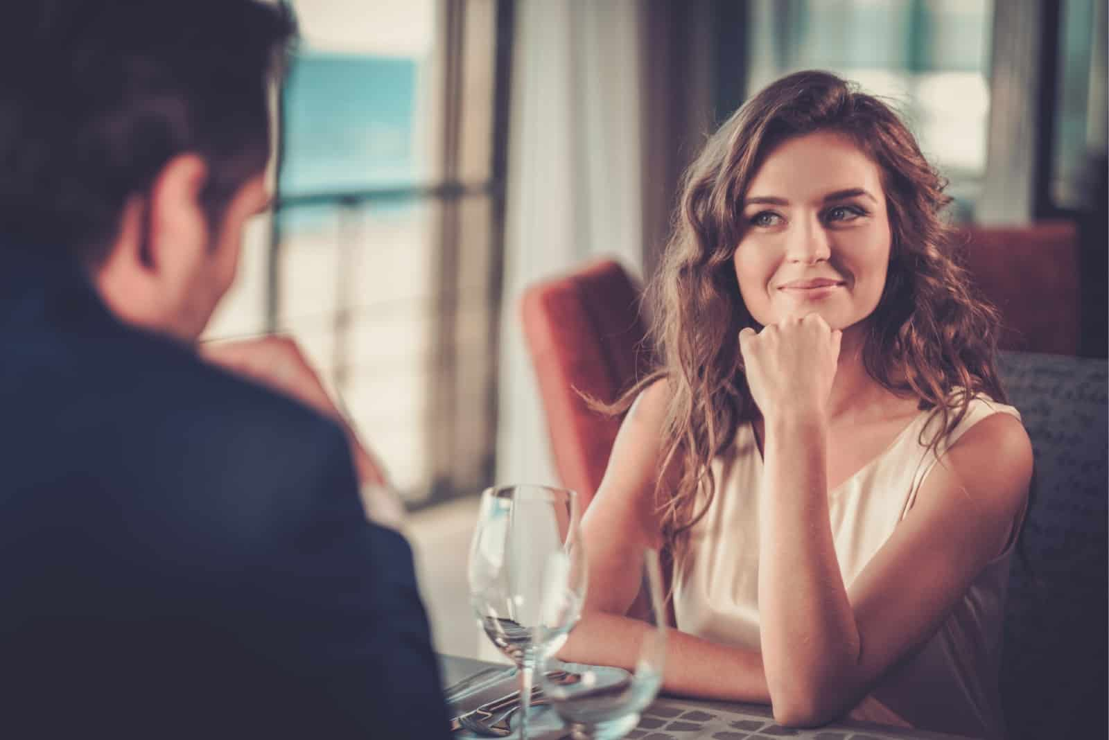 woman looking at man while sitting in restaurant