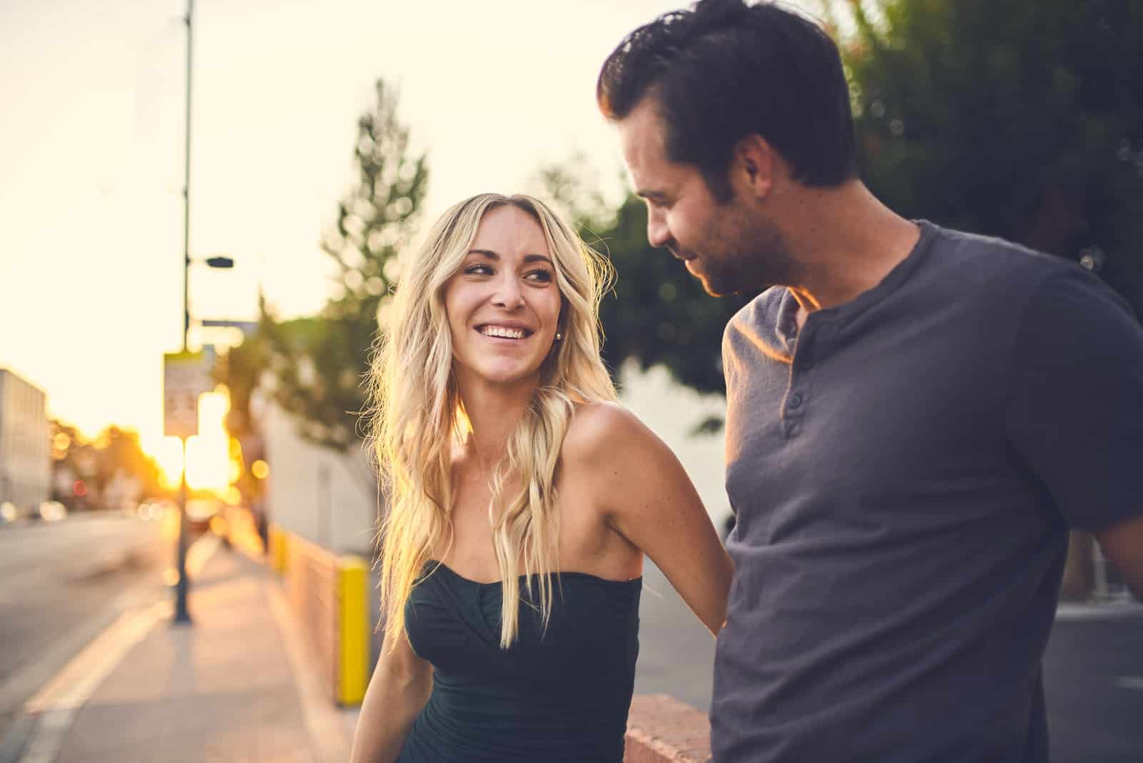 blonde woman smiling while looking at man outdoor