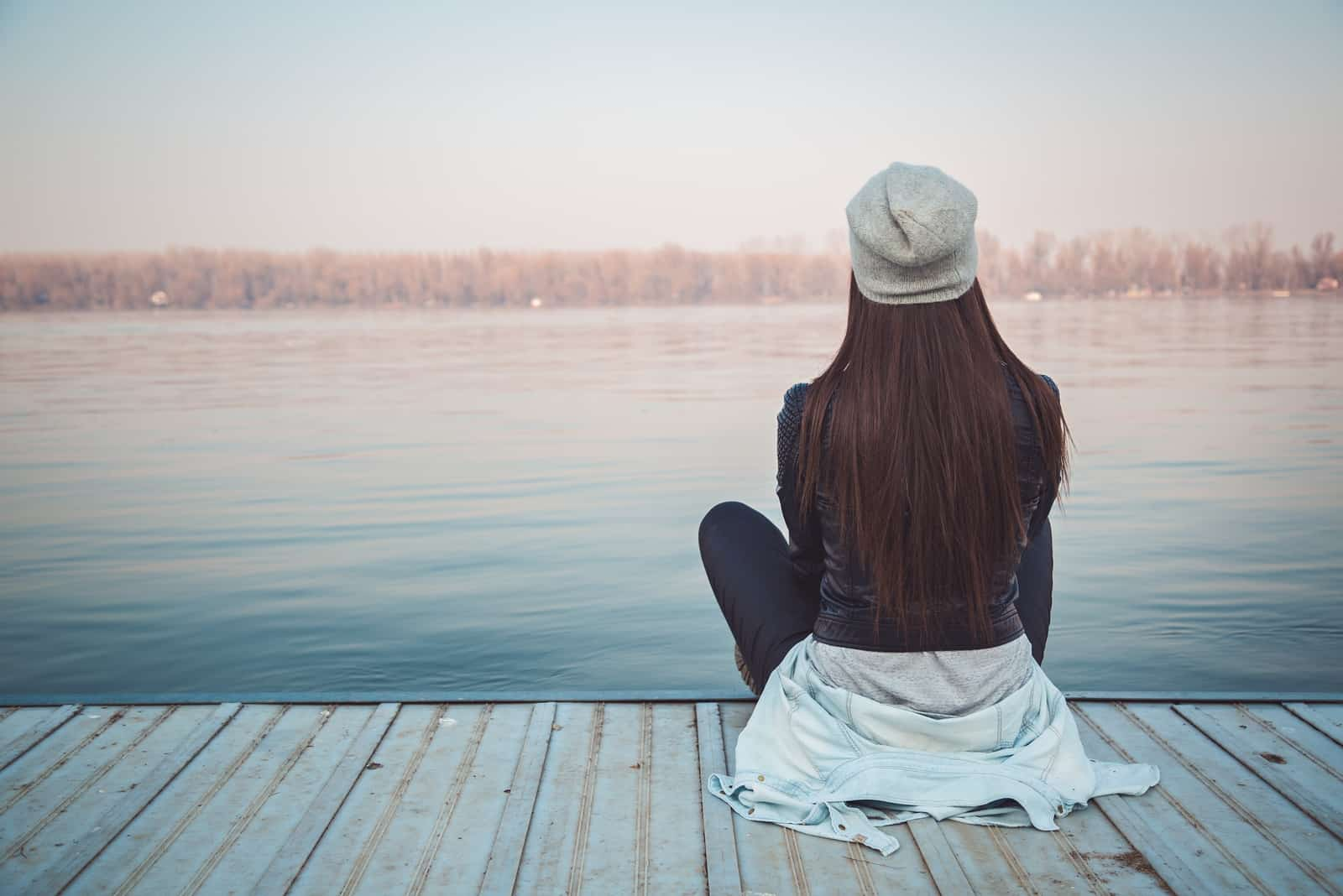 woman with gray hat sitting on dock looking at water