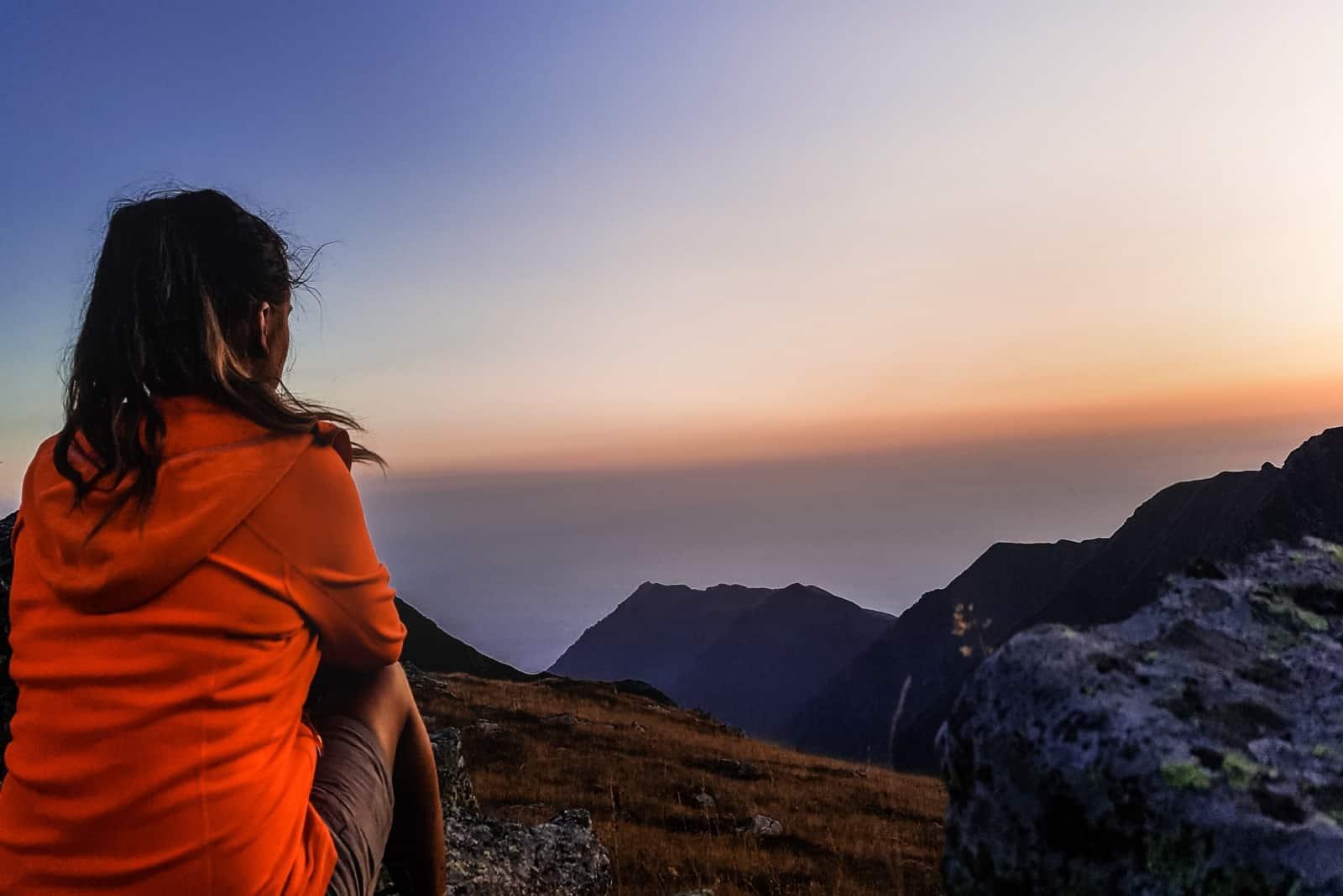 woman in orange jacket sitting on rock looking at mountain