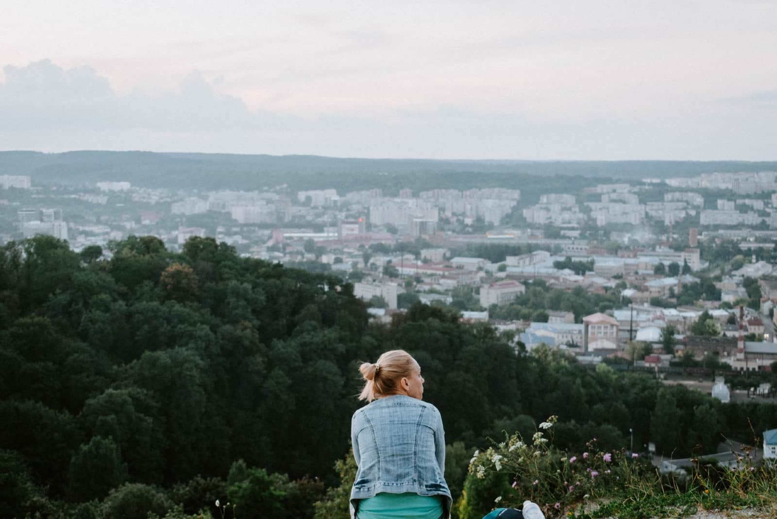 blonde woman in denim jacket sitting on top of hill