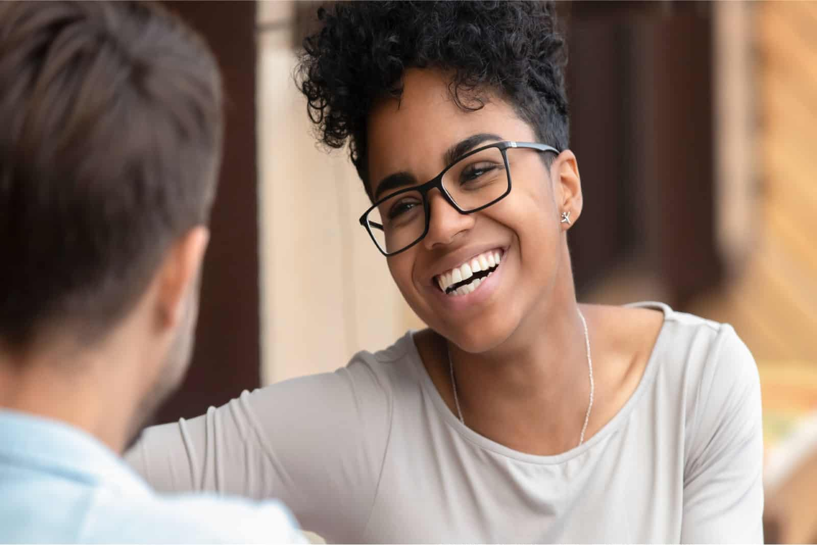 woman with curly hair smiling while looking at man