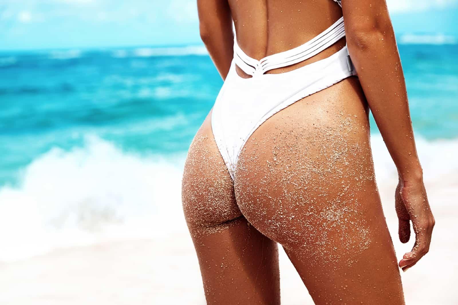 woman in white swimsuit standing near sea