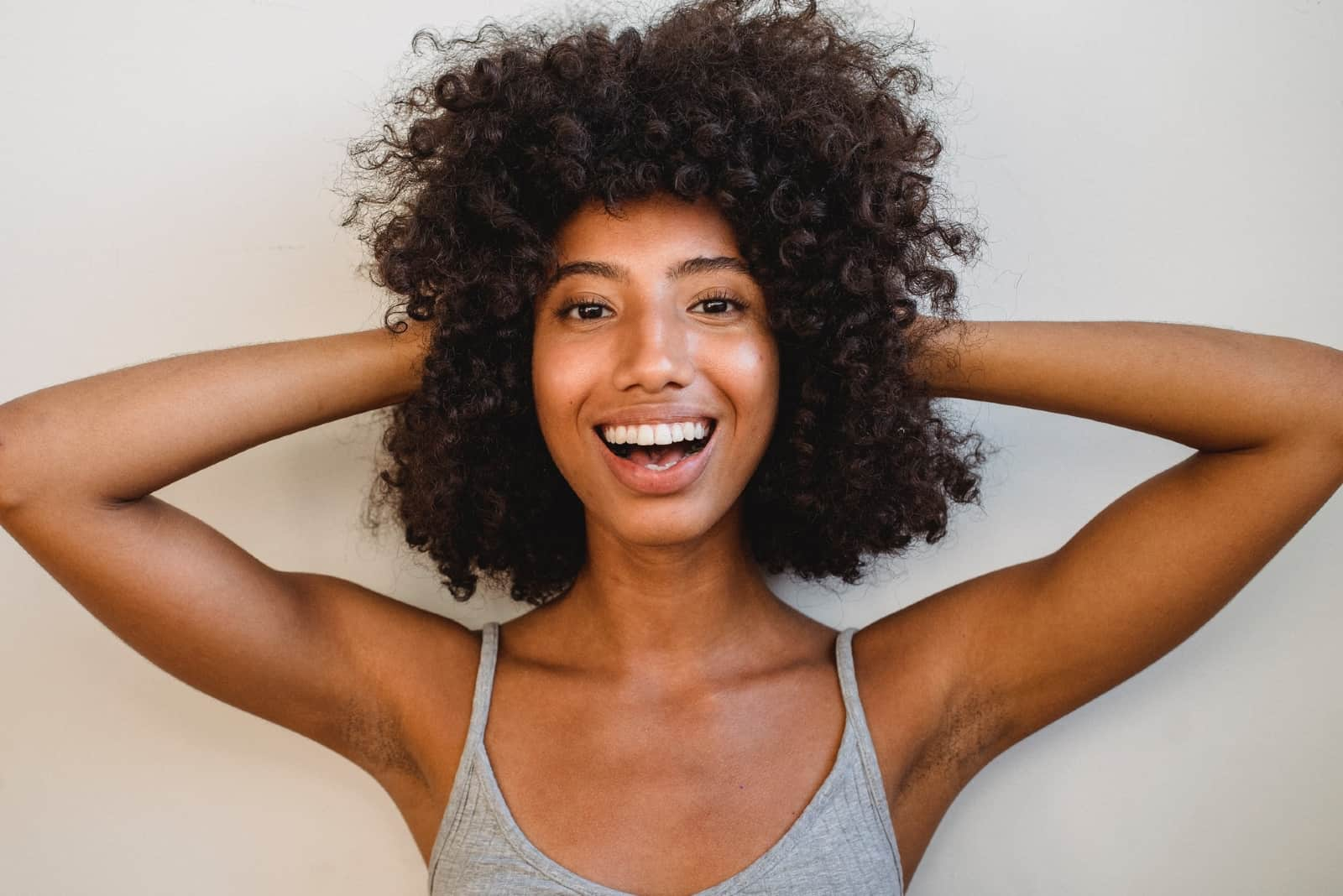 happy woman with curly hair standing near wall