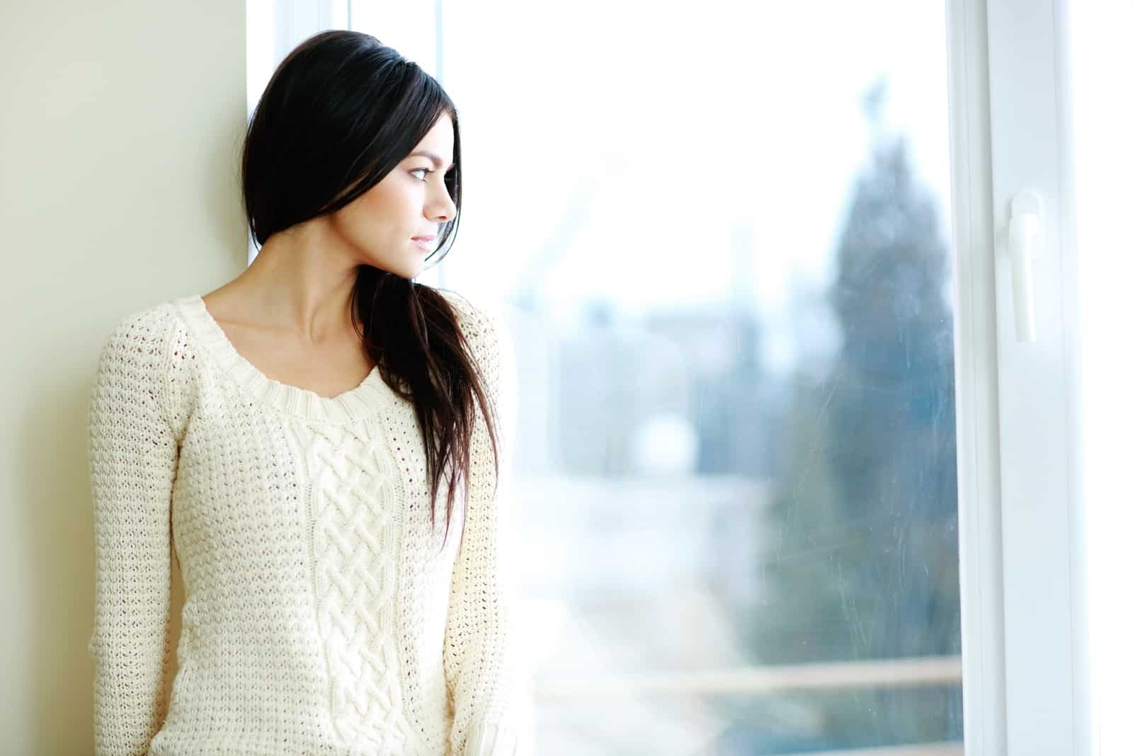 woman in white sweater standing near window