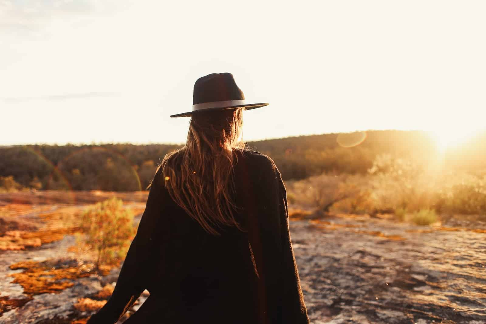woman with hat standing on rocks during sunset