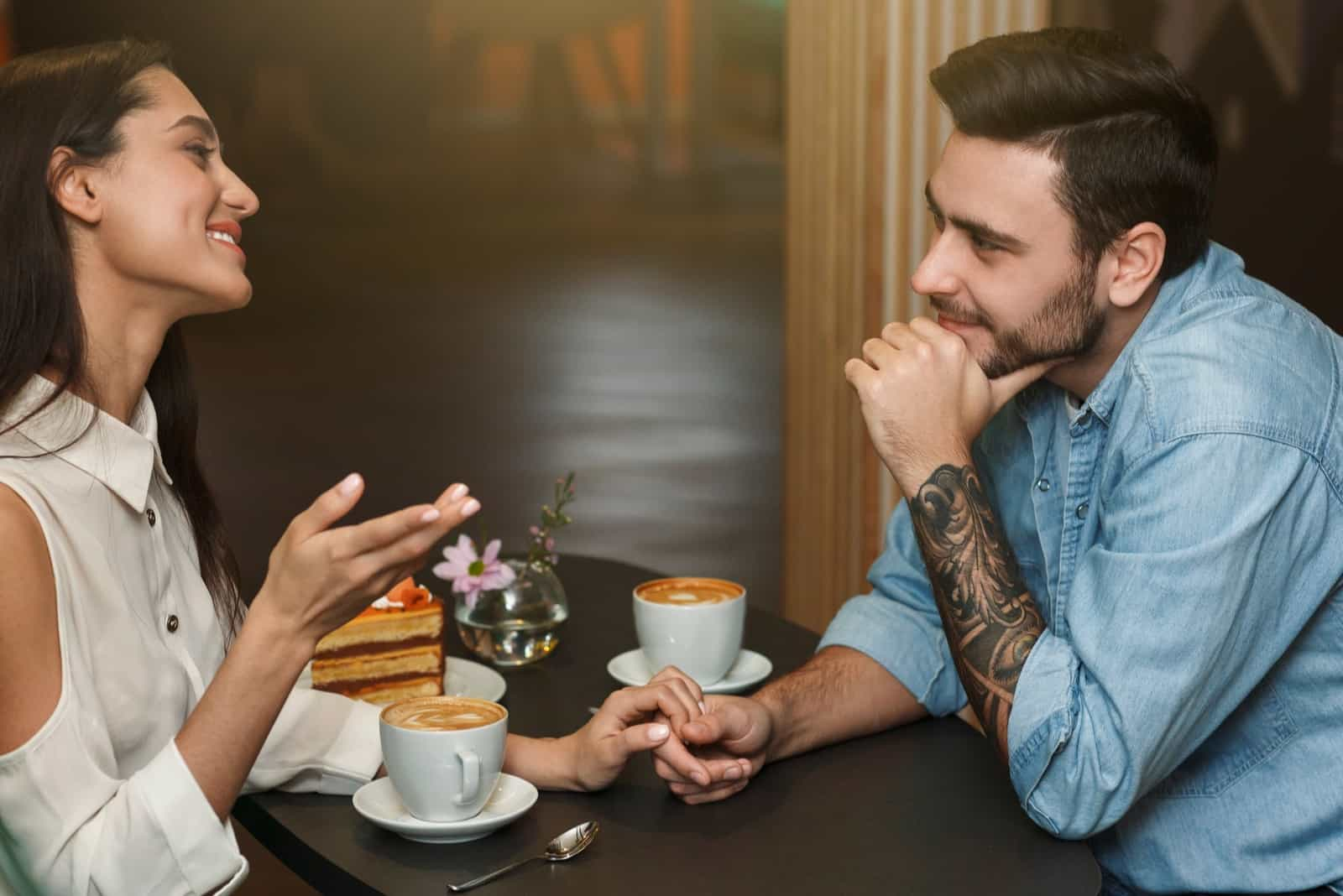 woman talking to man while sitting in cafe