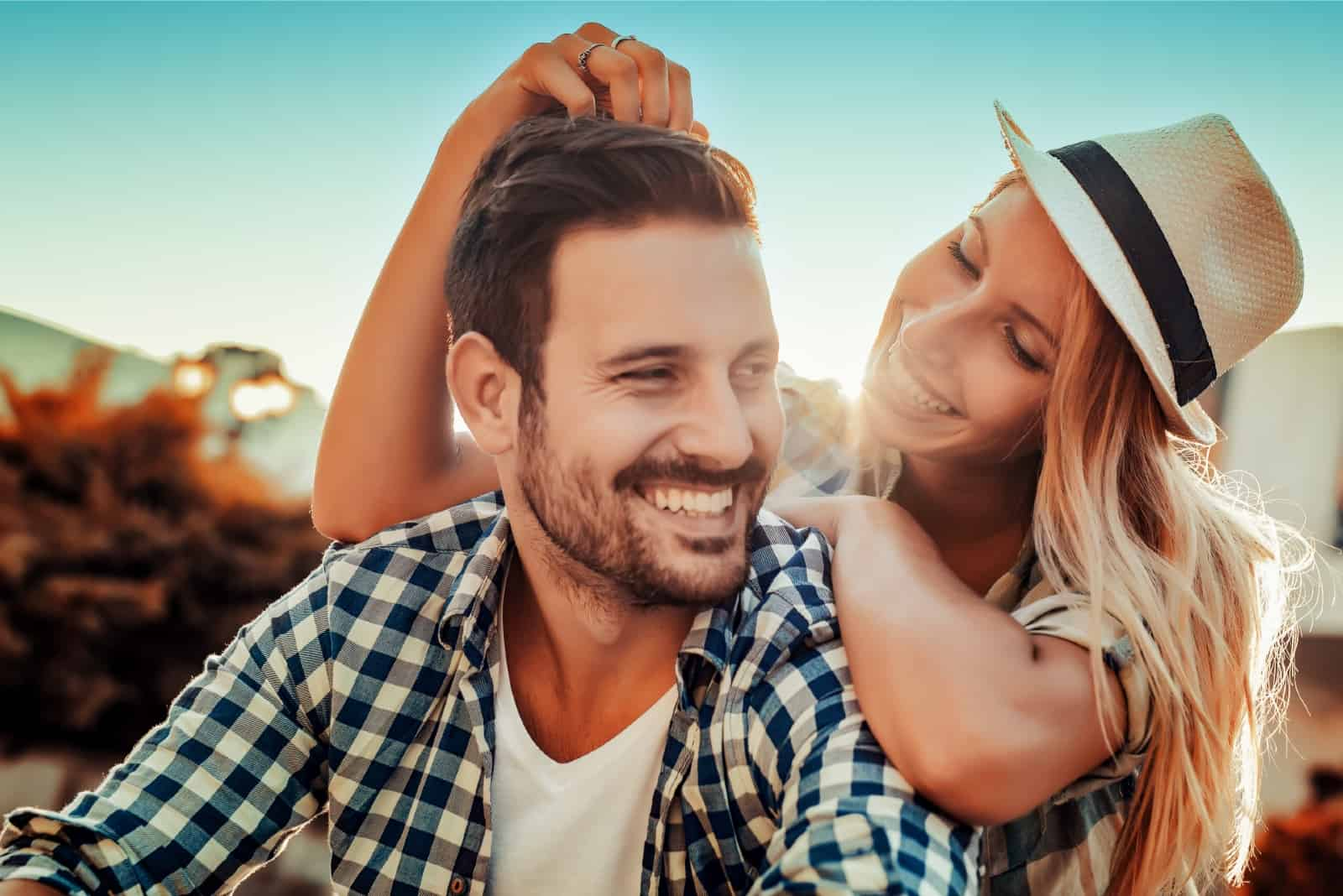 happy woman with hat touching man's hair outdoor