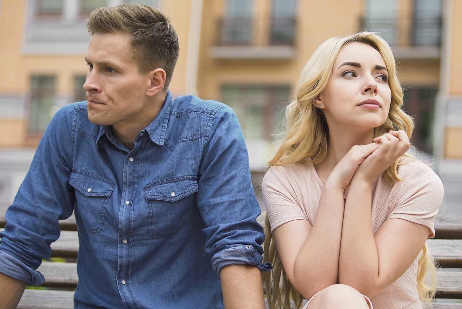 jealous man sitting beside his girlfriend