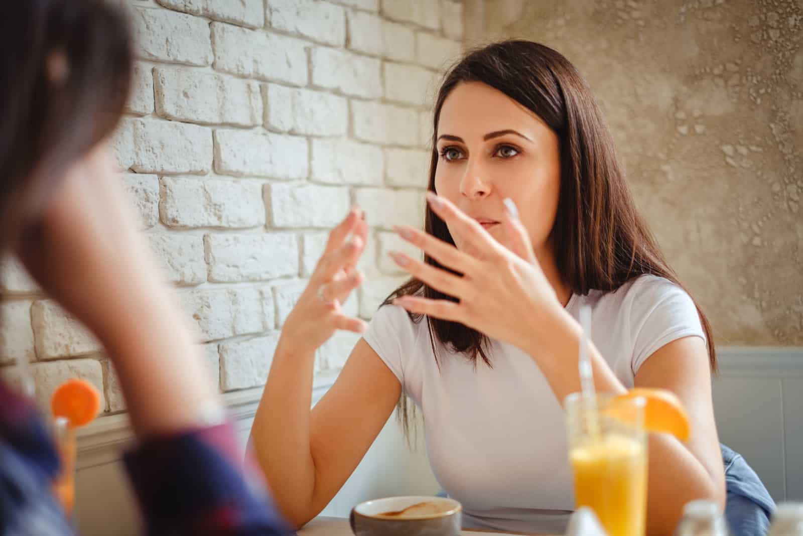 Girl explaining something with hands to her friend in the restaurant