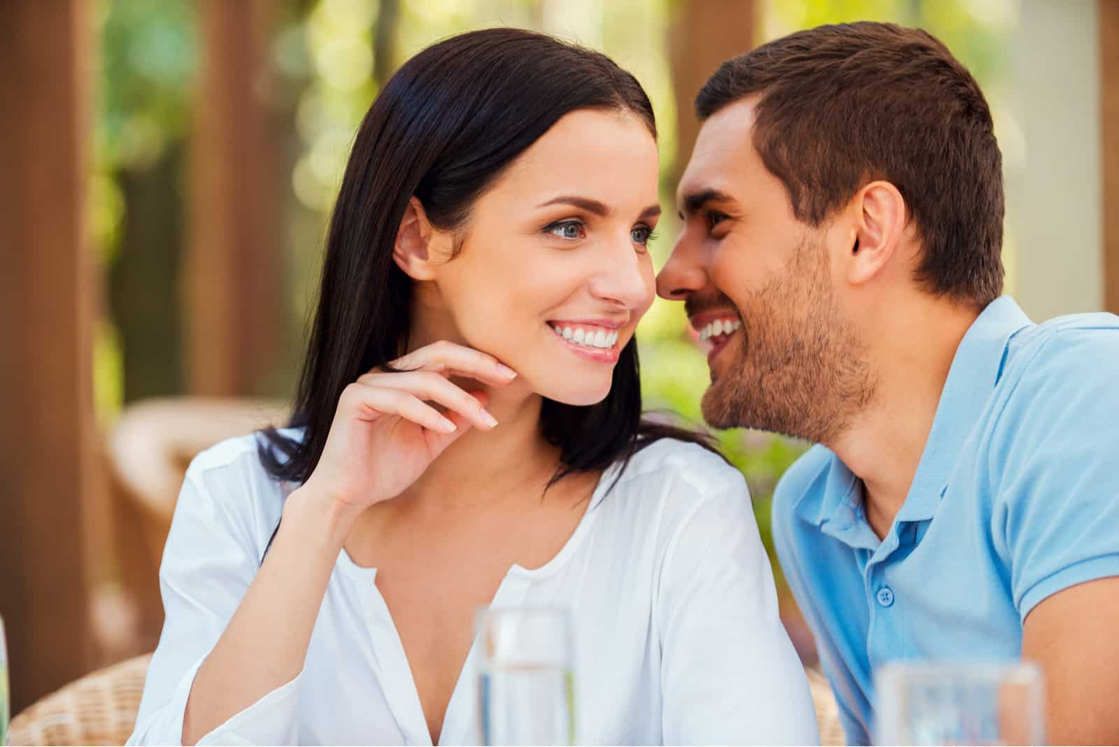 Handsome young man telling something to his girlfriend and smiling while sitting at the table outdoors together