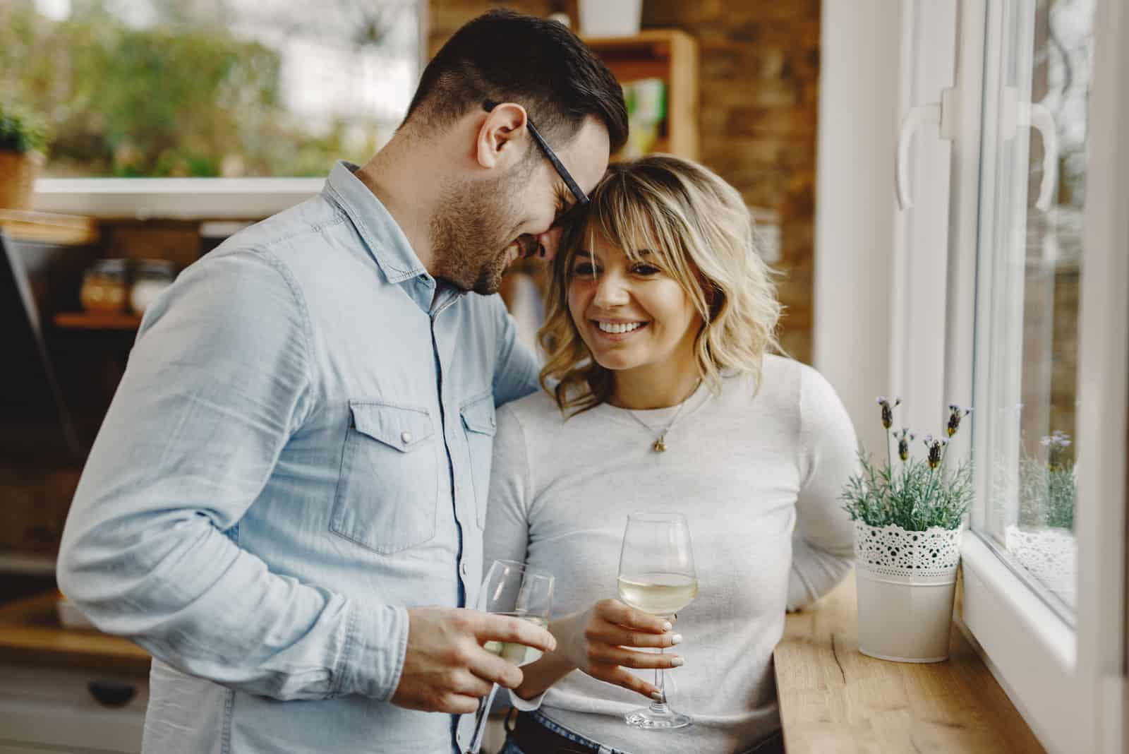 Happy couple in love drinking wine by the window in the kitchen