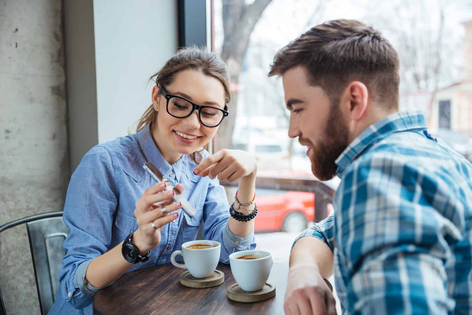 Happy couple using smartphone together and drinking coffee in cafe