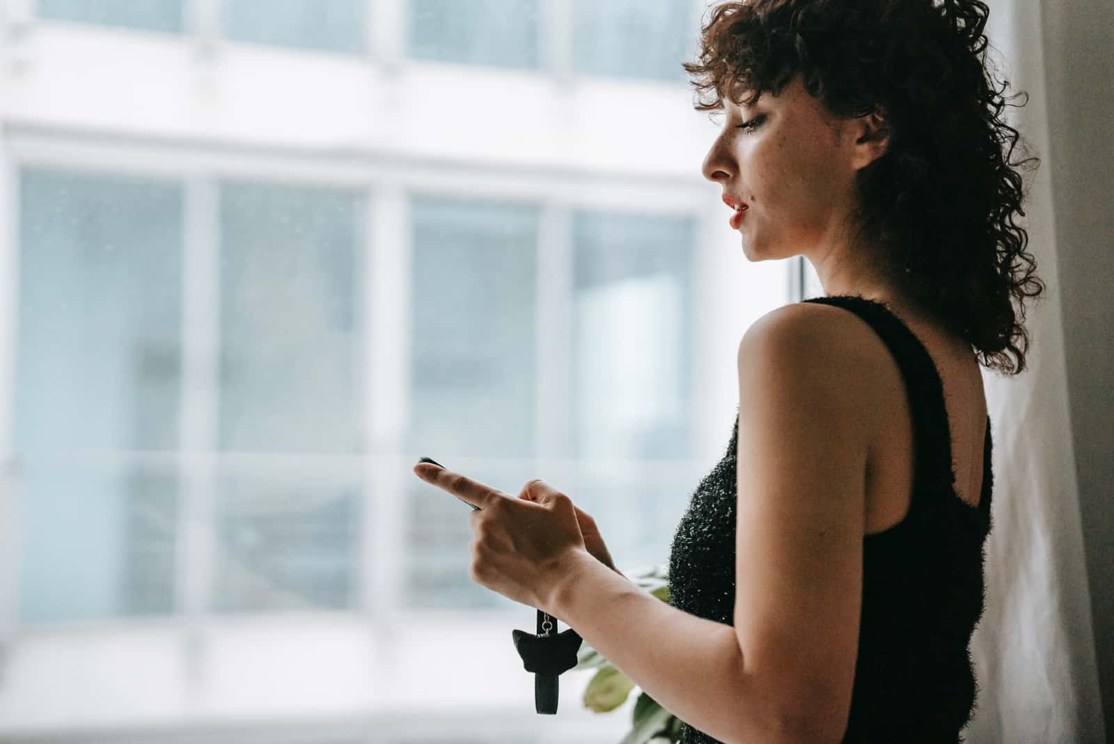 woman holding smartphone while standing near window