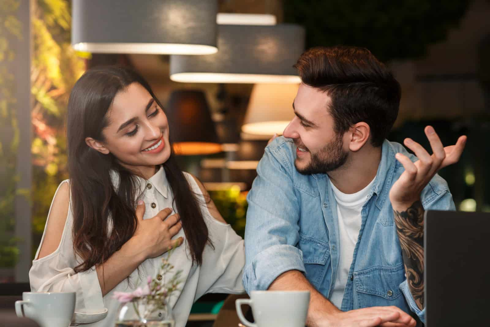 an attractive girl in a cafe flirts with a bearded man