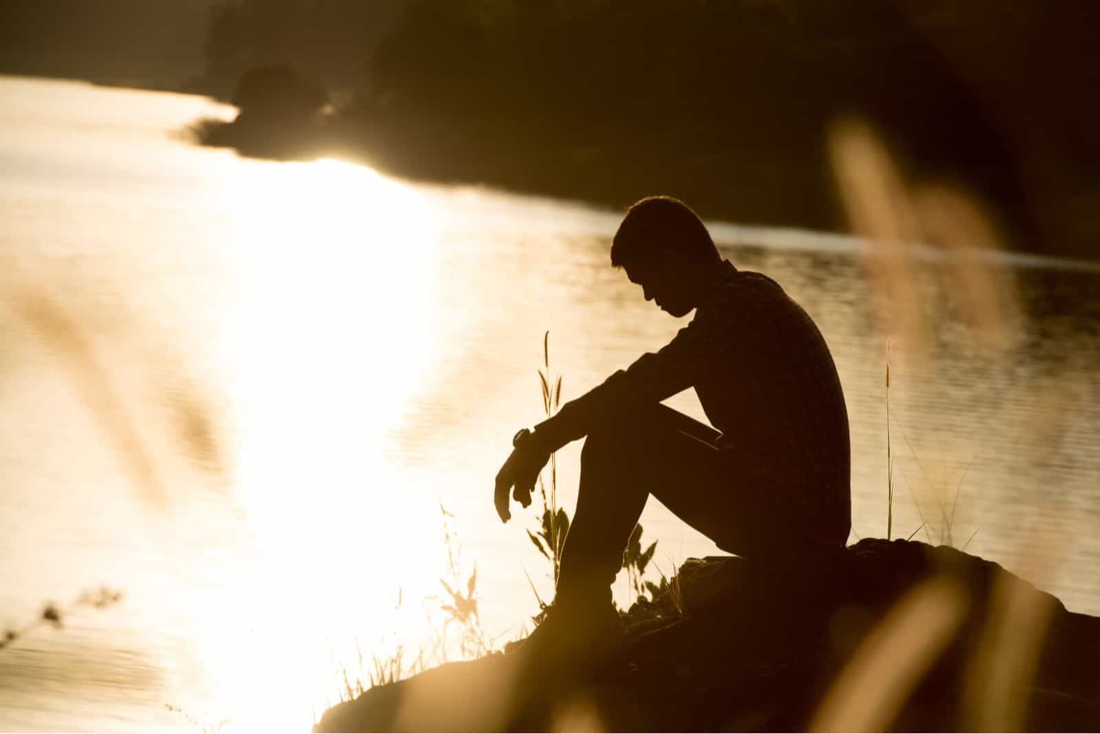 Sad young man at sunset by the river