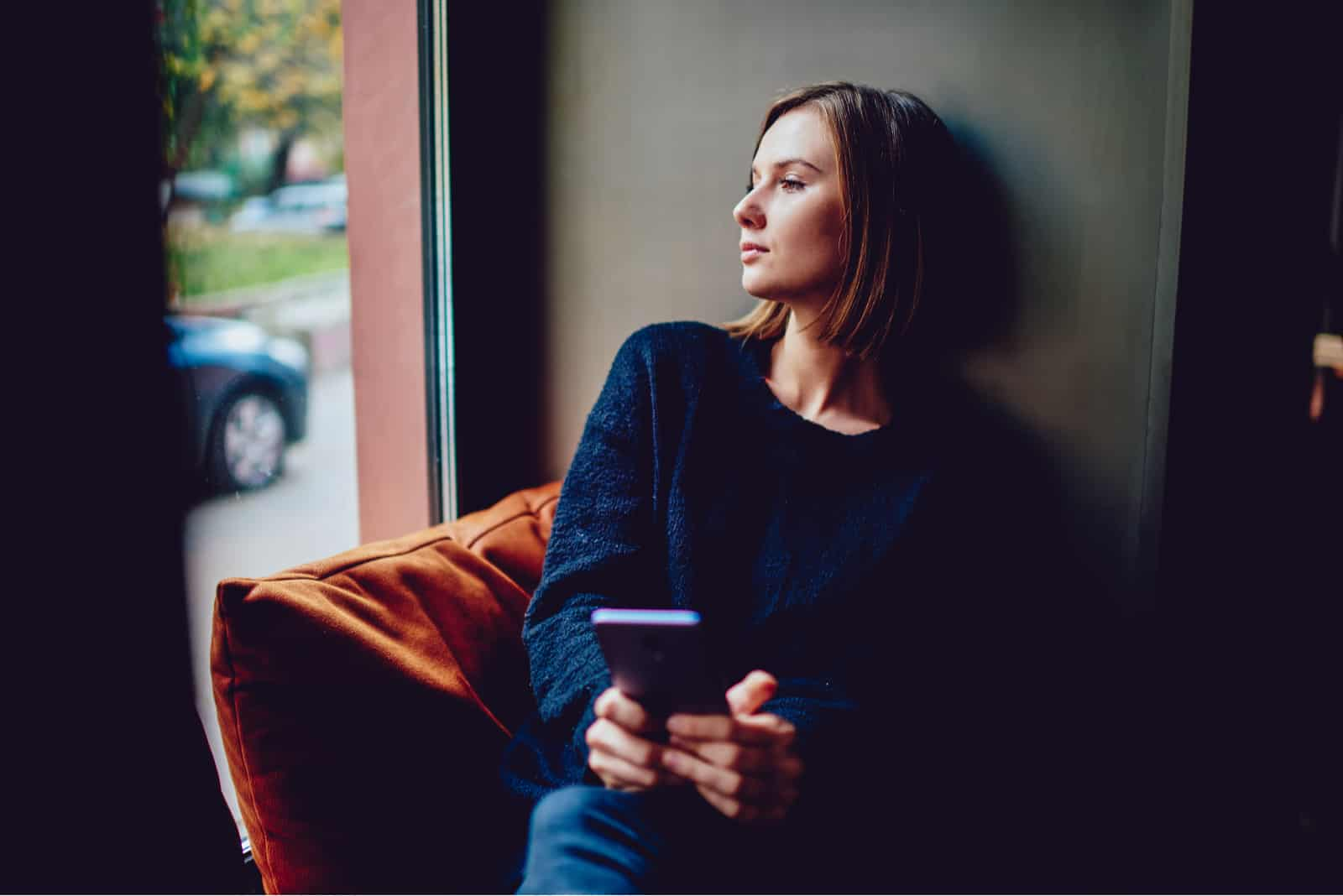 Thoughtful young woman holding her smartphone