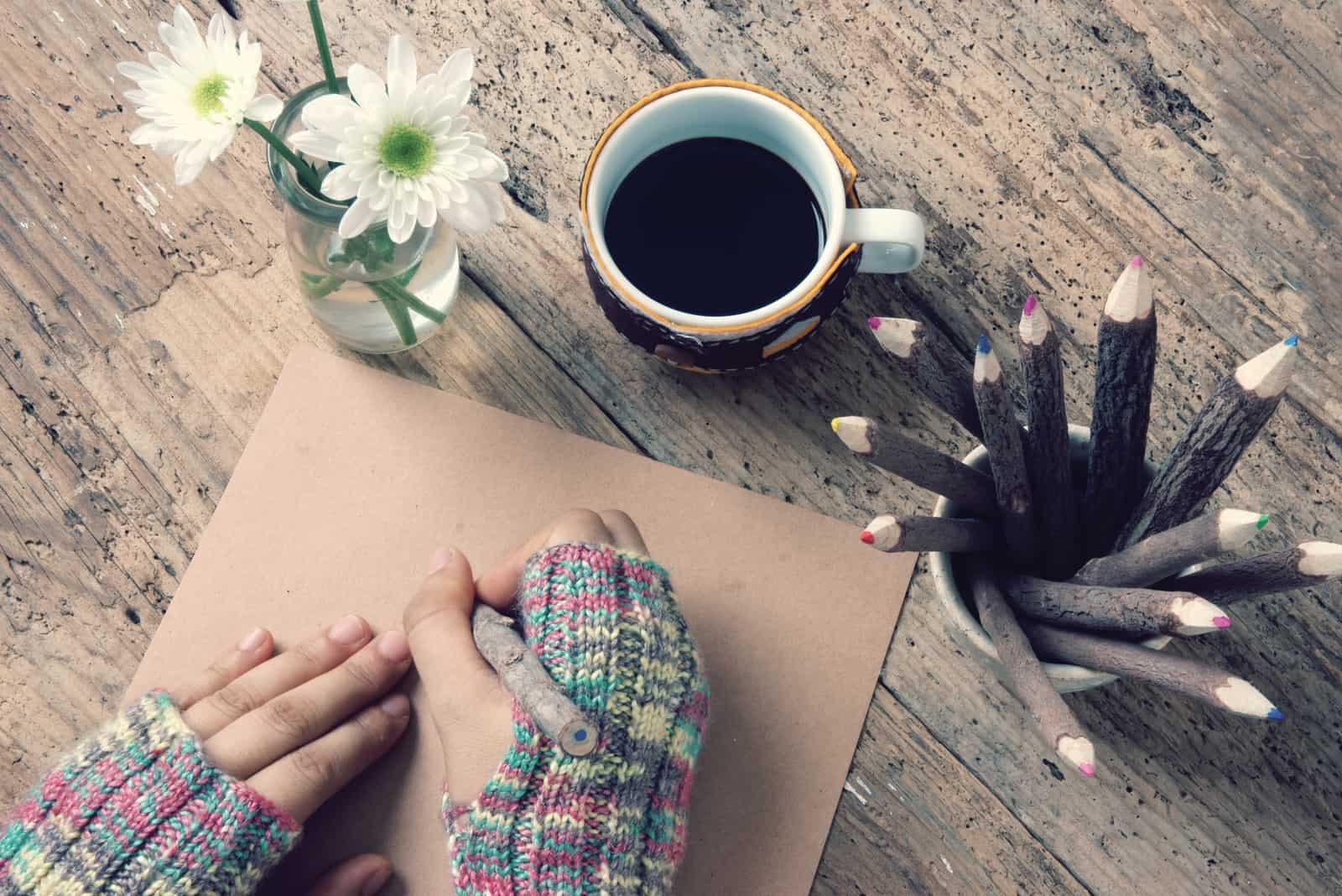 Women hand wear wool gloves in wintertime, writting letter for him