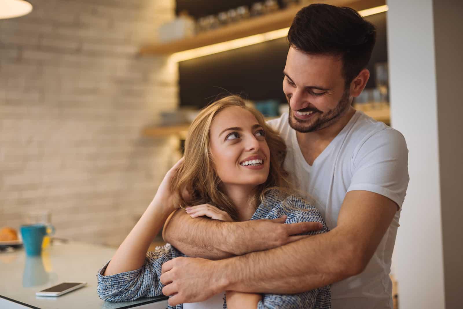 a bearded man in the kitchen hugs a happy blonde