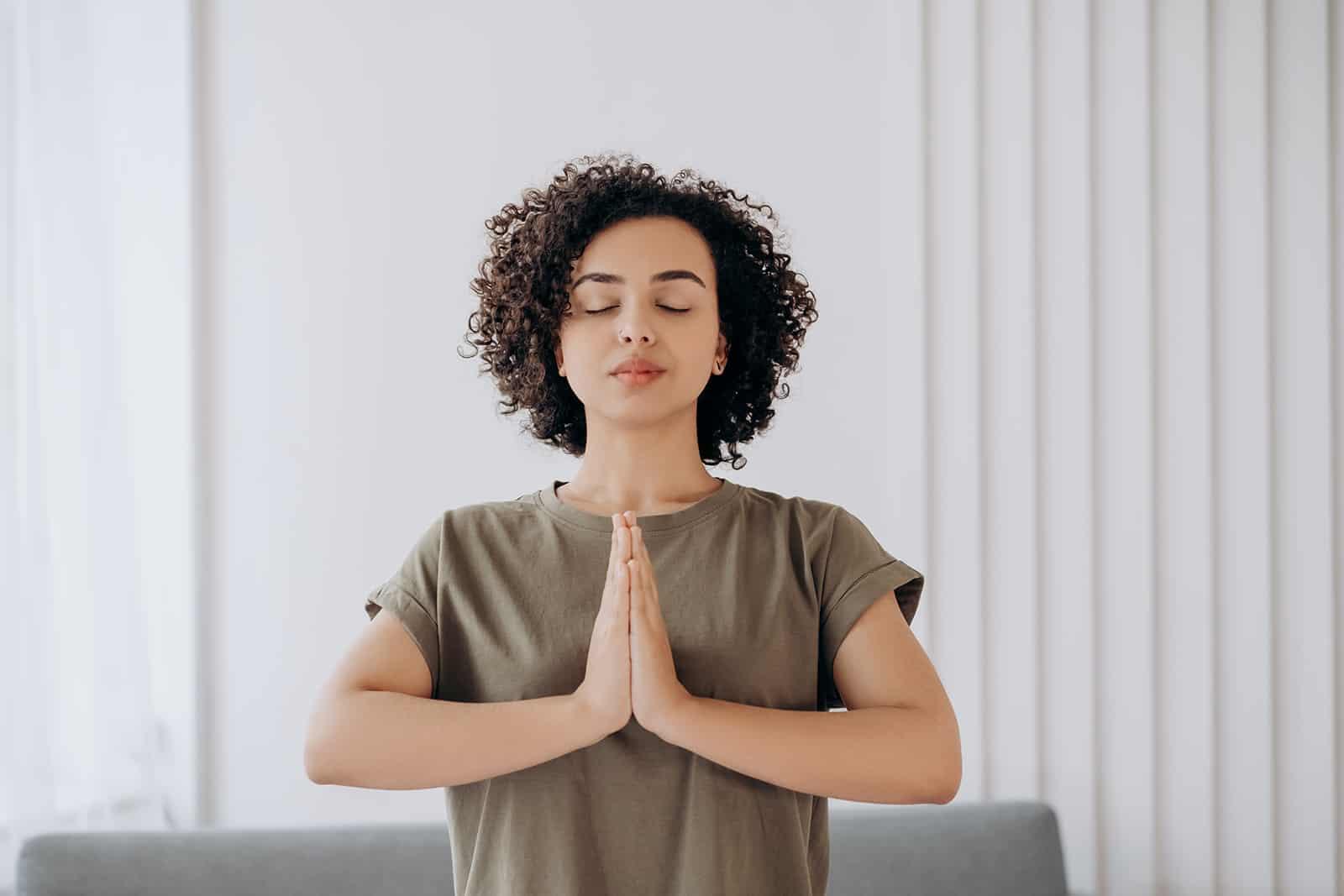 a calm woman meditating at home