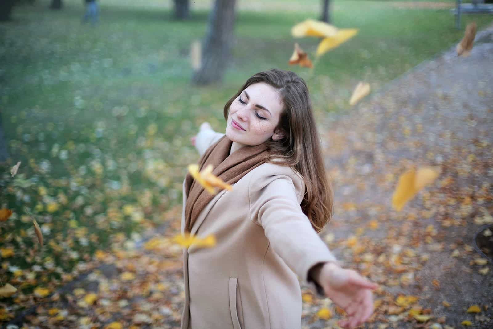 a calm woman standing under the falling leaves with eyes closed