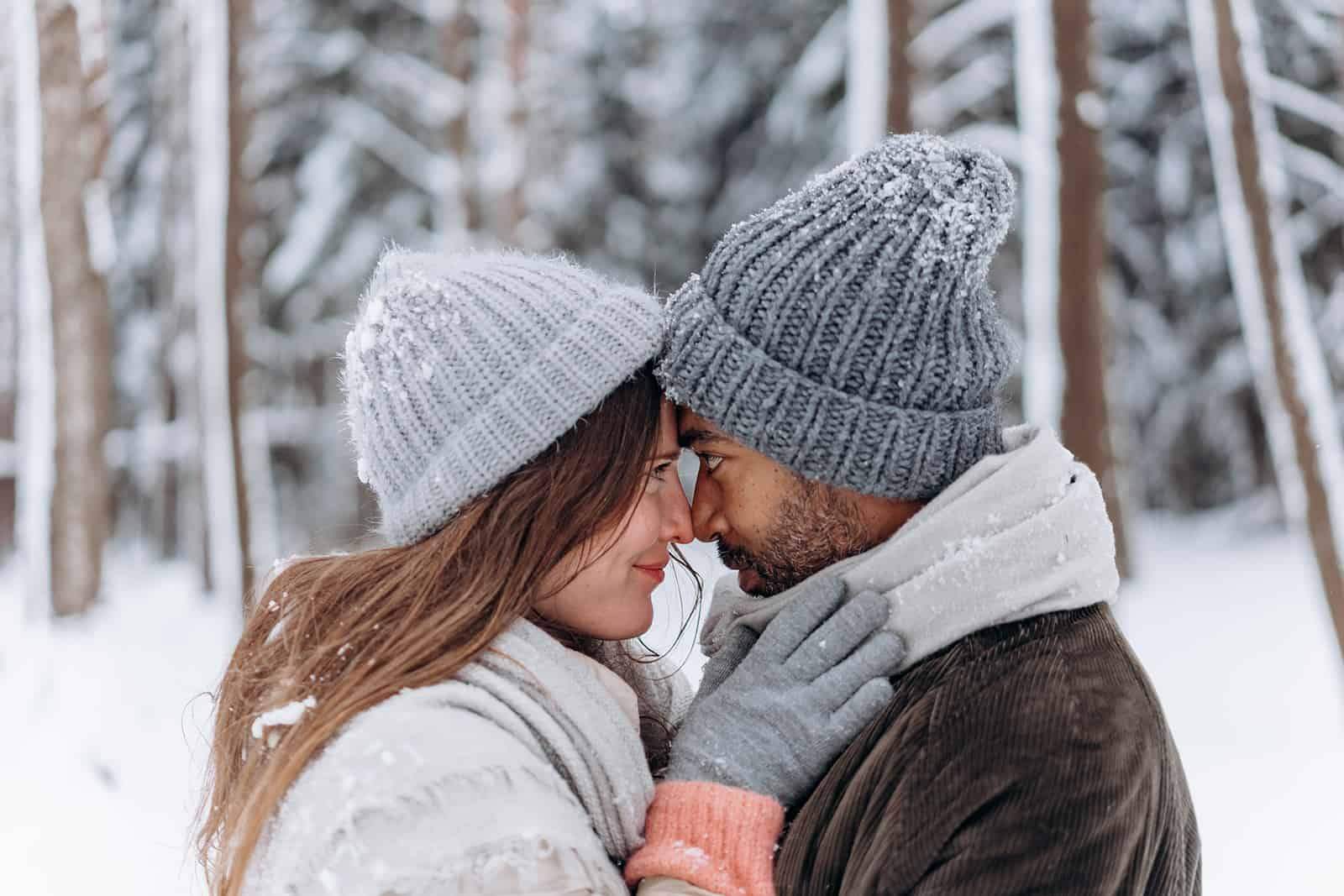 a couple facing each other at snowy weather