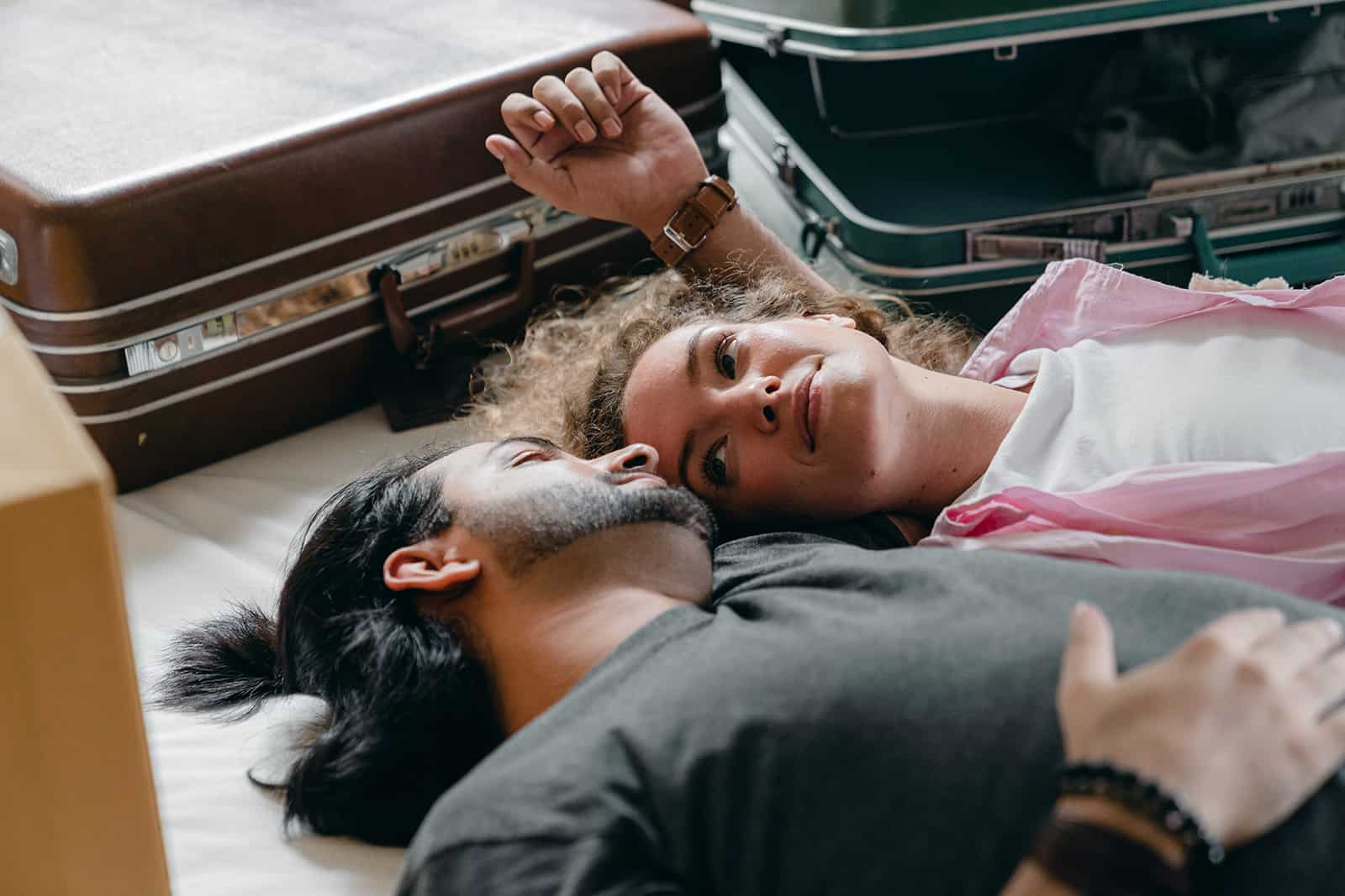 a couple resting on the bed on moving day