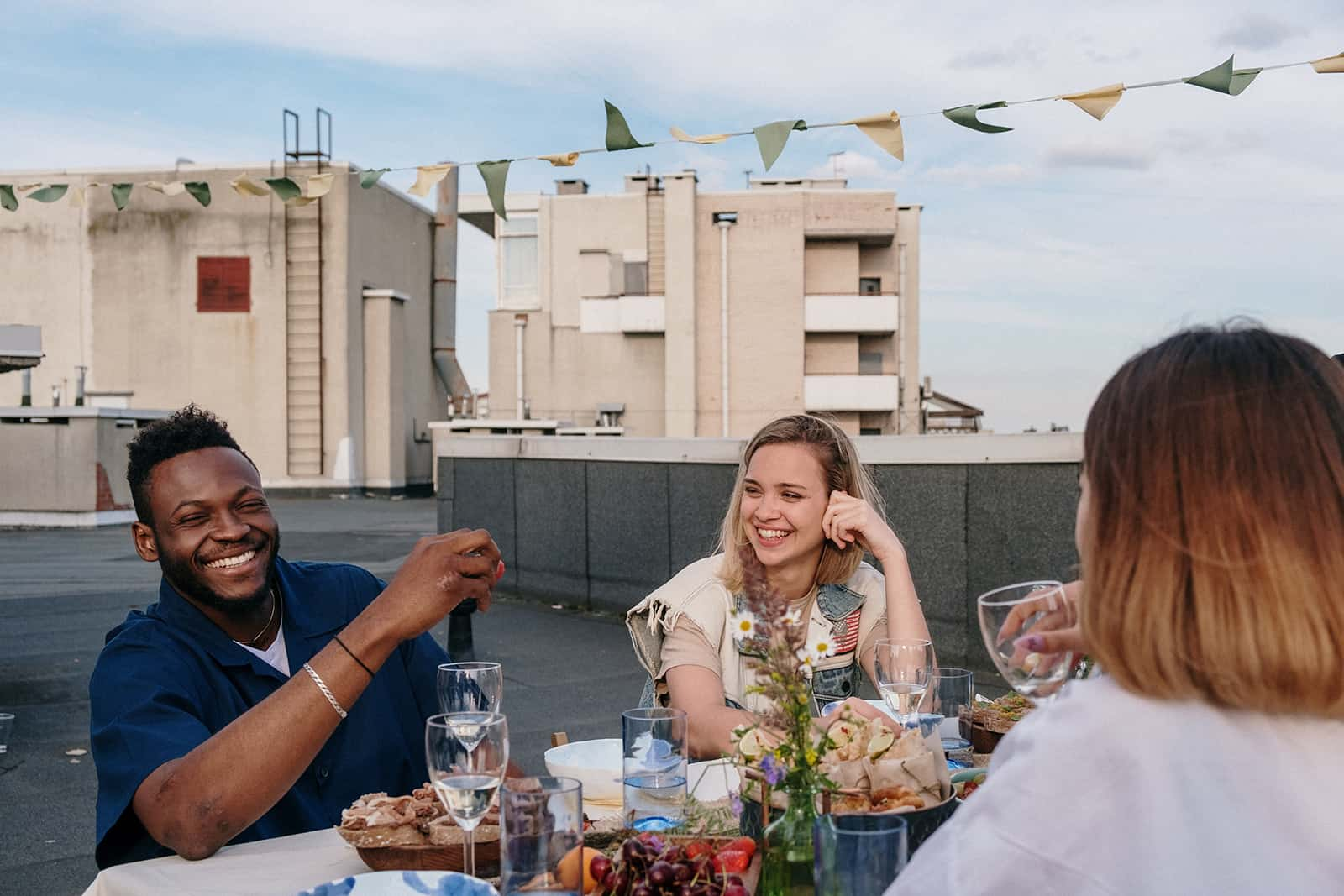 a group of friends having fun while sitting at the table at the party on the rooftop