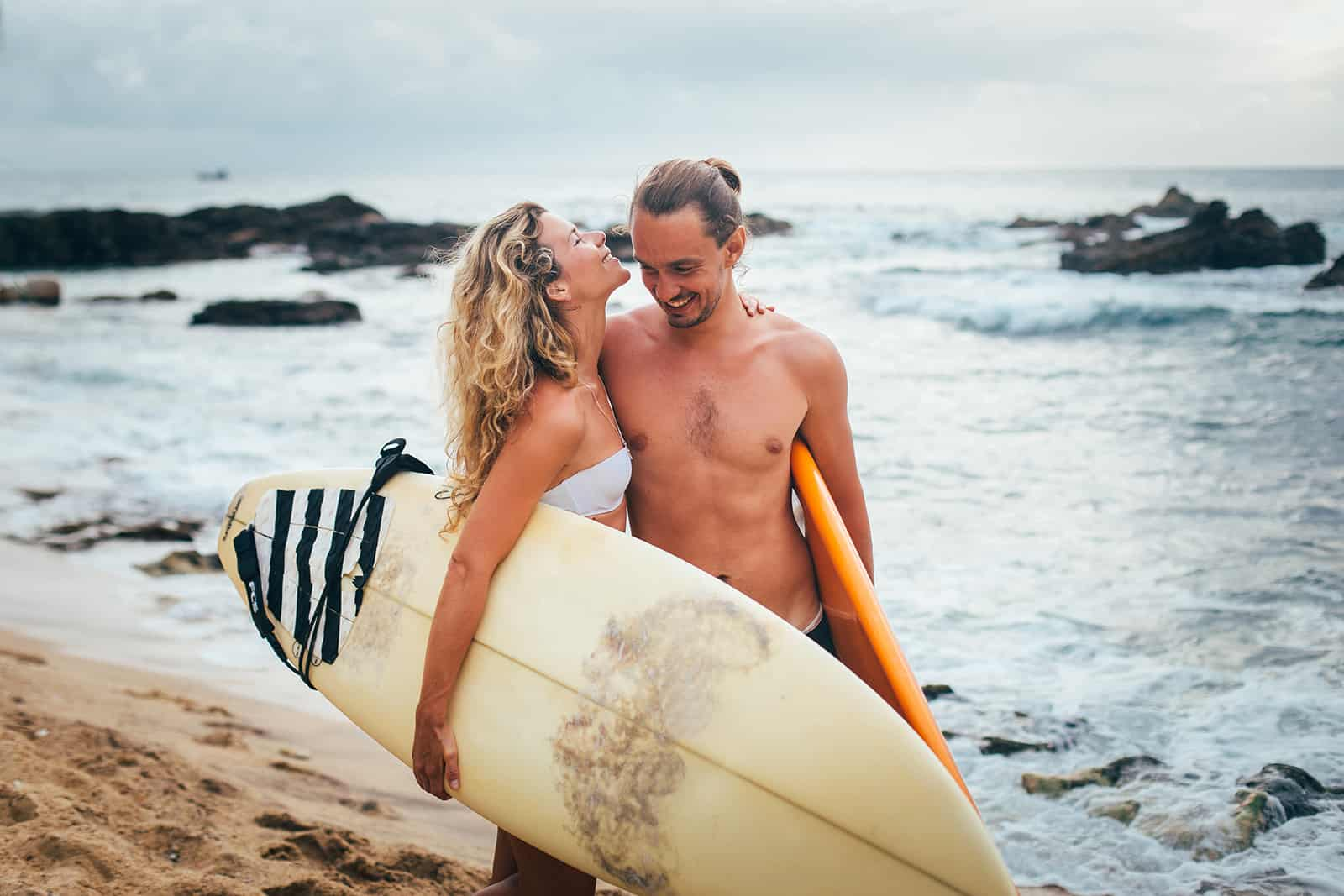a happy couple carrying surfing boards and walking on the beach