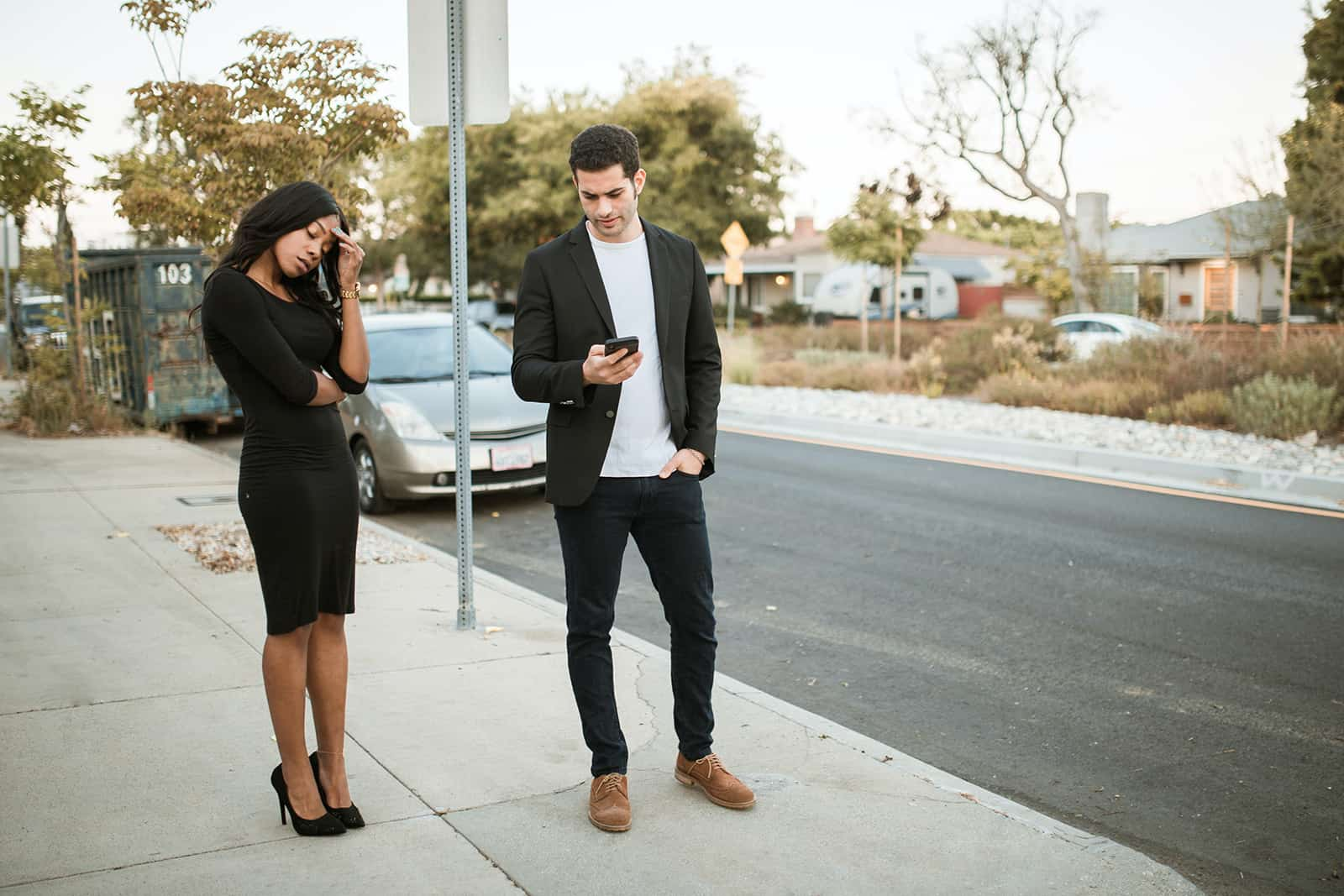 a jealous man checking smartphone of his girlfriend while standing together on the sidewalk