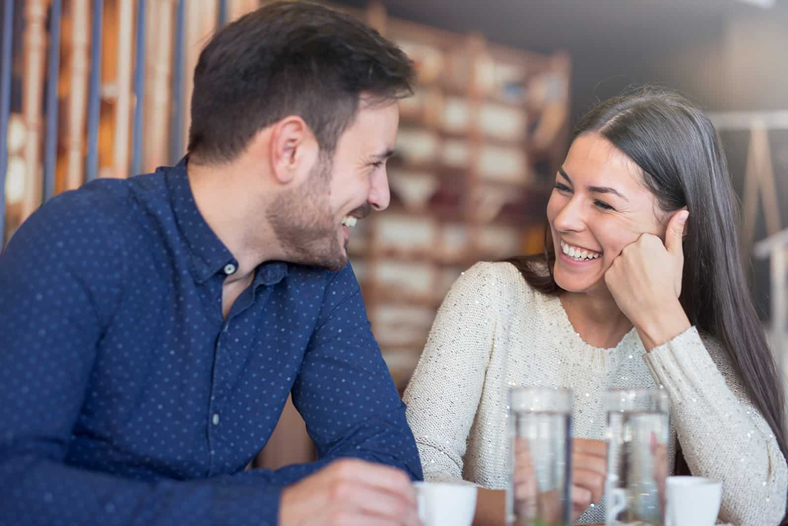 a laughing couple sitting in the cafe and enjoying conversation