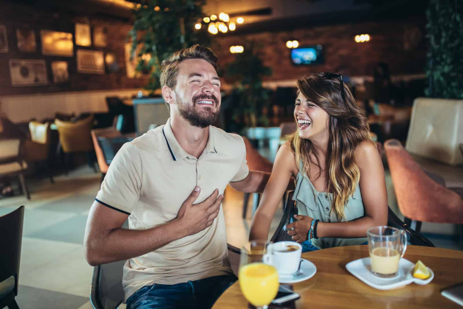 a loving couple in a cafe laughing