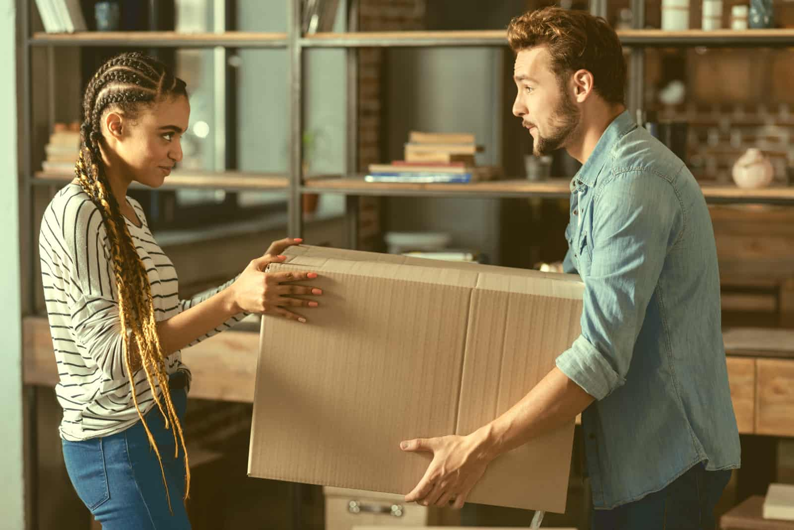 a man and a woman hold a cardboard package